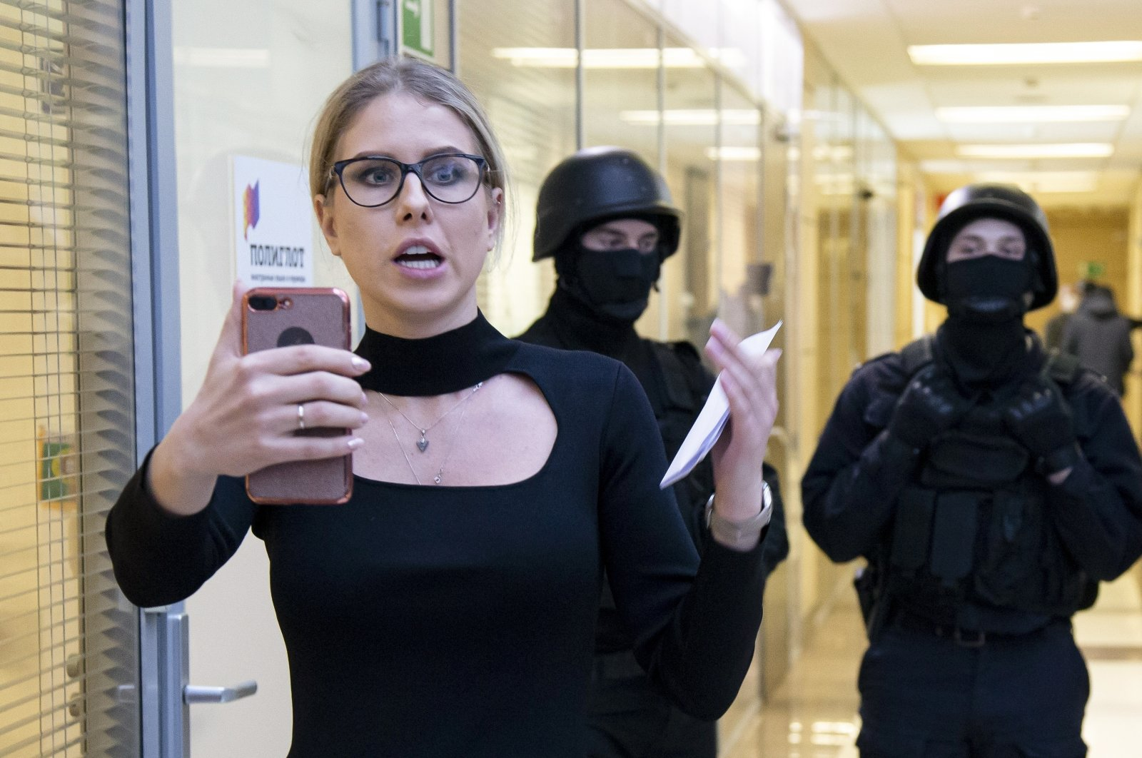Russian opposition activist Lyubov Sobol speaks on the phone as police stand guard at the Foundation for Fighting Corruption office in Moscow, Russia, Dec. 26, 2019. (AP Photo)