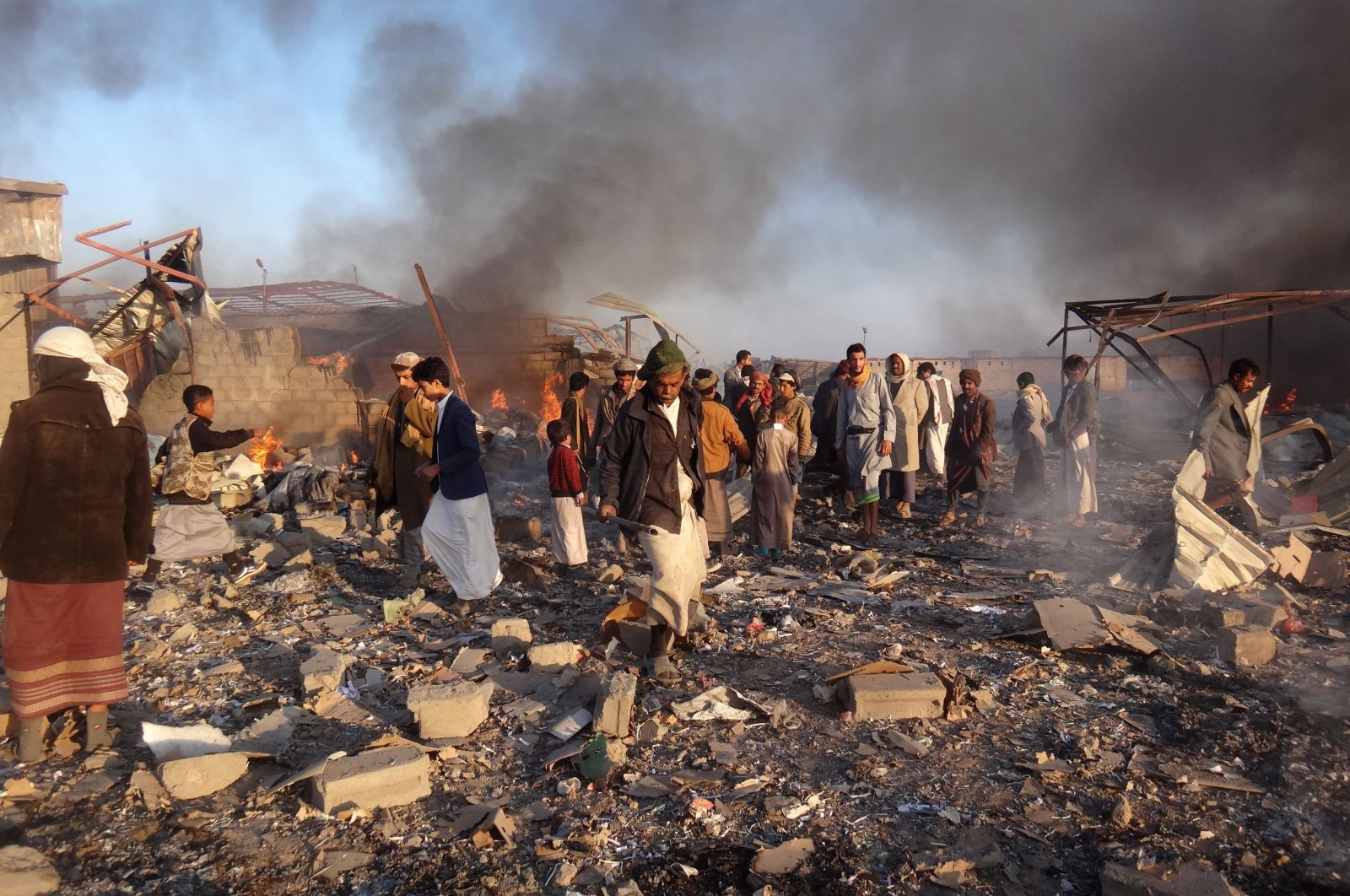 Smoke rises as Yemenis inspect the damage at the site of airstrikes in the northwestern Houthi-held city of Saada, Jan. 06, 2018.