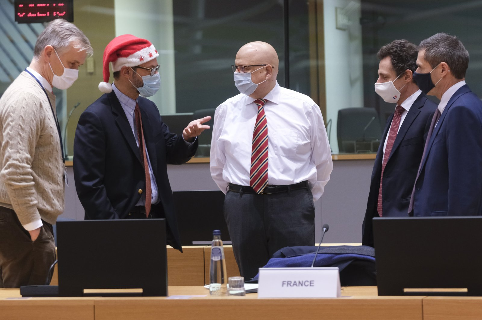 A colleague wears a Christmas hat as he speaks with EU ambassadors and representatives during a special meeting of Coreper, at the European Council building in Brussels, Belgium, Dec. 25, 2020. (AP Photo)