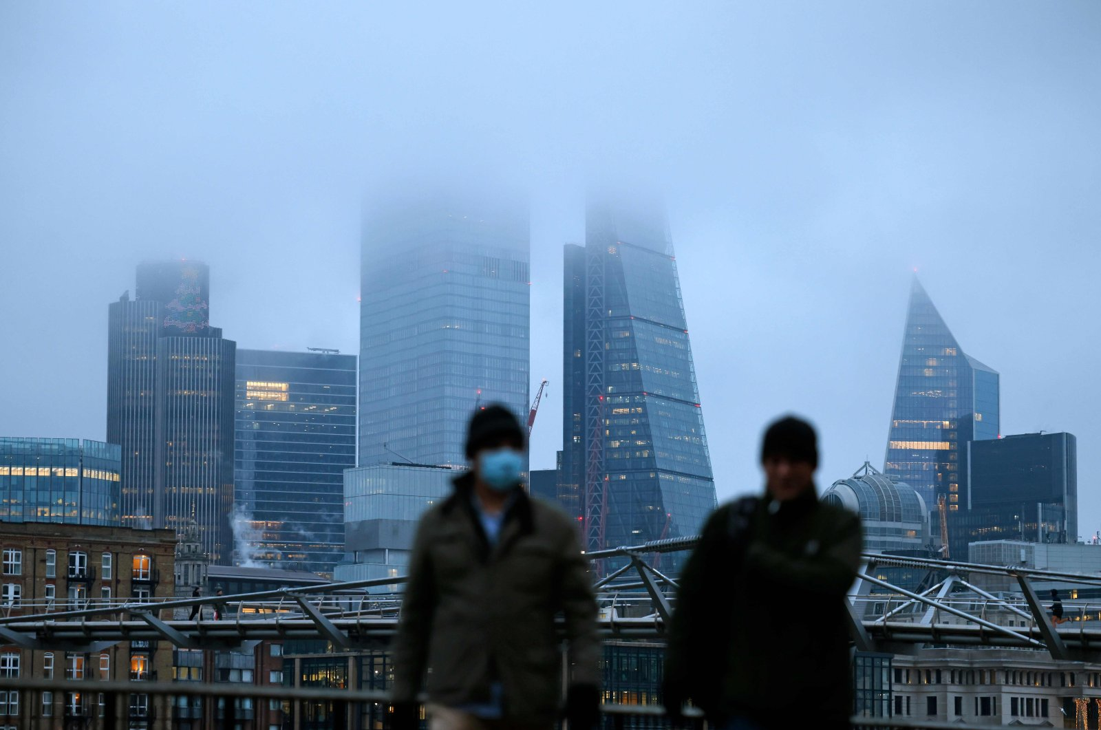 Pedestrians walk on the South Bank as mist covers buildings in the City of London on the bank holiday, Dec. 28, 2020 (AFP Photo)