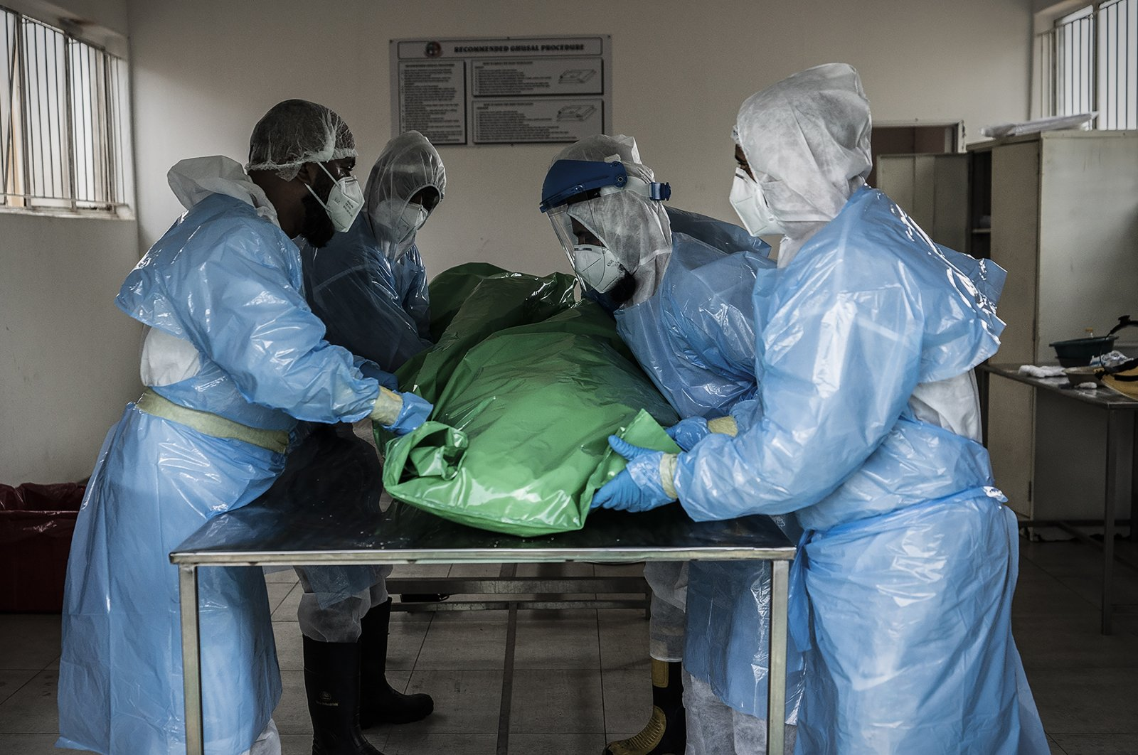 Members of the Saaberie Chishty Burial Society prepare the body of a person who died from COVID-19 at the Avalon Cemetery in Lenasia, Johannesburg Saturday Dec. 26, 2020. (AP Photo)