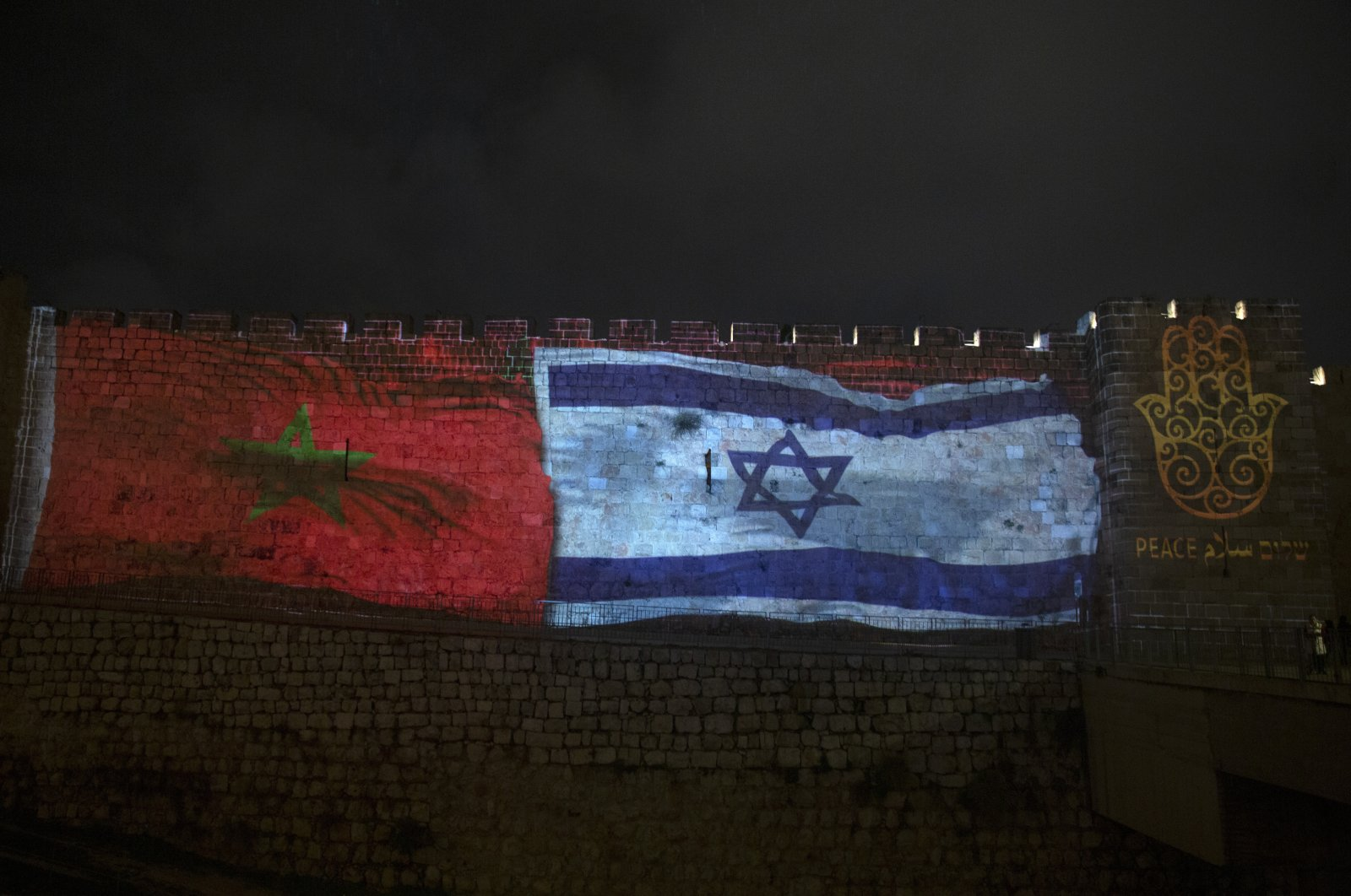 """The national flags of Israel and Morocco are projected on the walls of the Old City of Jerusalem, along with the word """"peace,"""" in English, Hebrew, and Arabic, Dec. 23, 2020. (AP Photo)"""