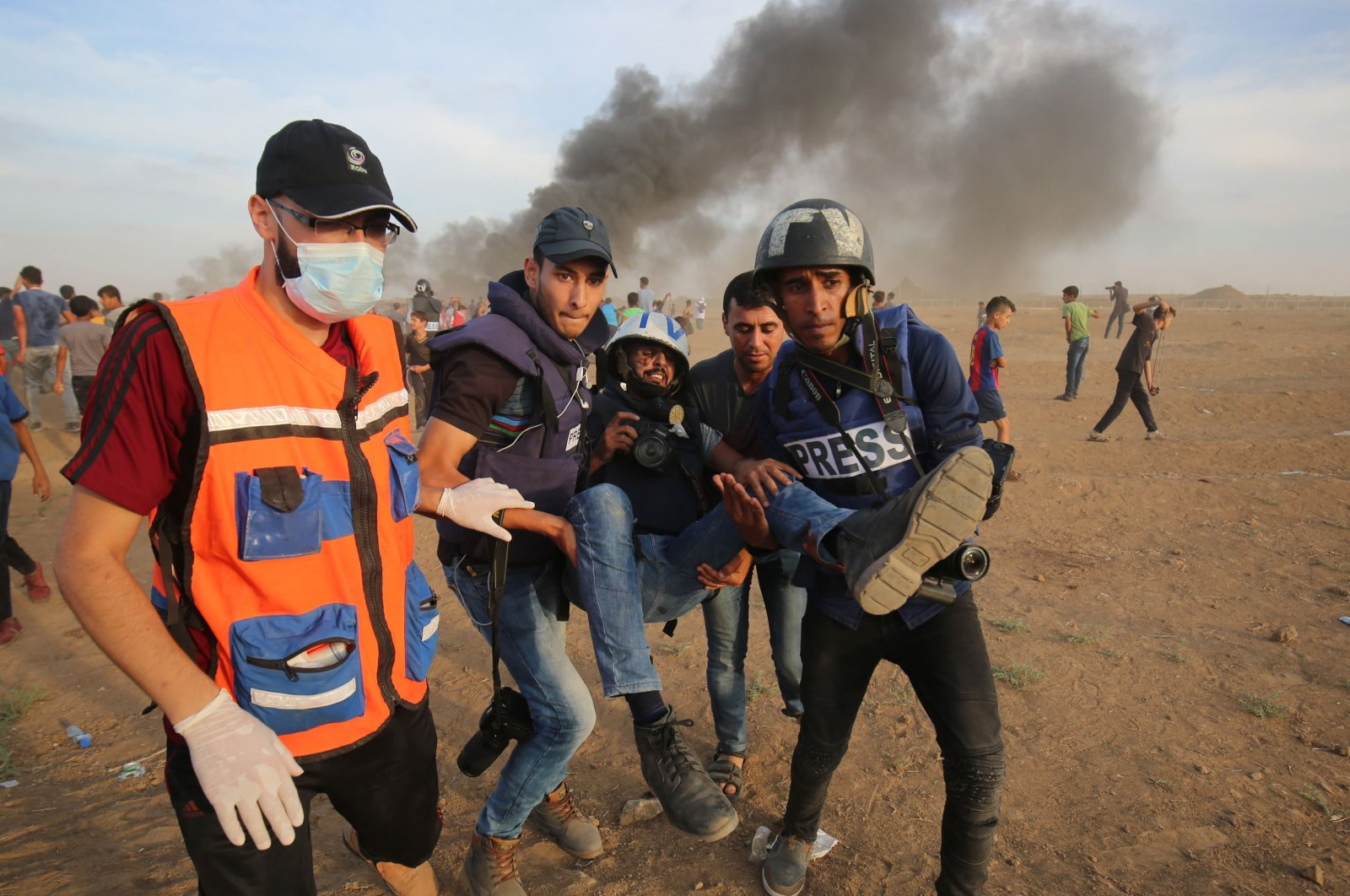 Palestinian paramedics and journalists carry a wounded fellow journalist during clashes with Israeli forces east of Gaza city, along the Gaza-Israel border in the Gaza Strip, Oct. 5, 2018. (AFP Photo)