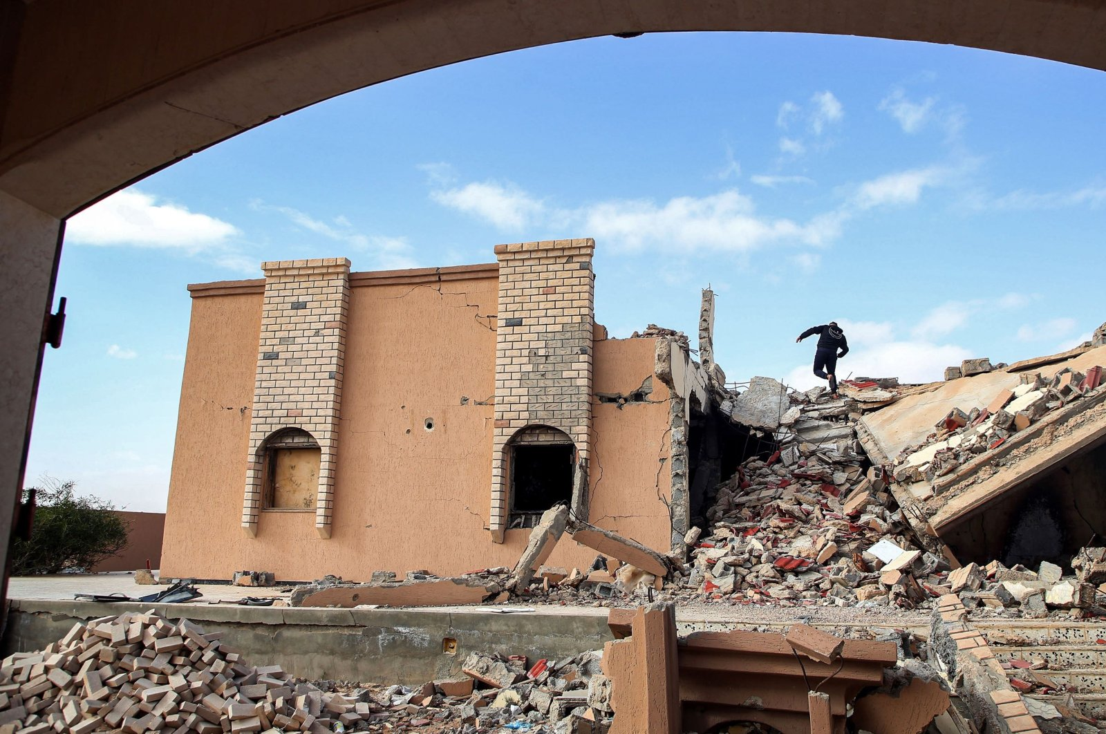 A youth climbs the rubble of a destroyed building in the city of Tawergha, some 200 kilometers (125 miles) east of Libya's capital close to the port city of Misrata, on Dec. 12, 2020. (AFP Photo)