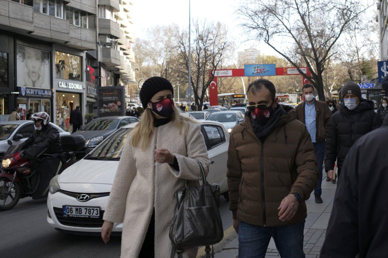 People wearing masks walk along a street hours before a two-day weekend lockdown, in Ankara, Turkey, Dec. 25, 2020. (AP Photo)