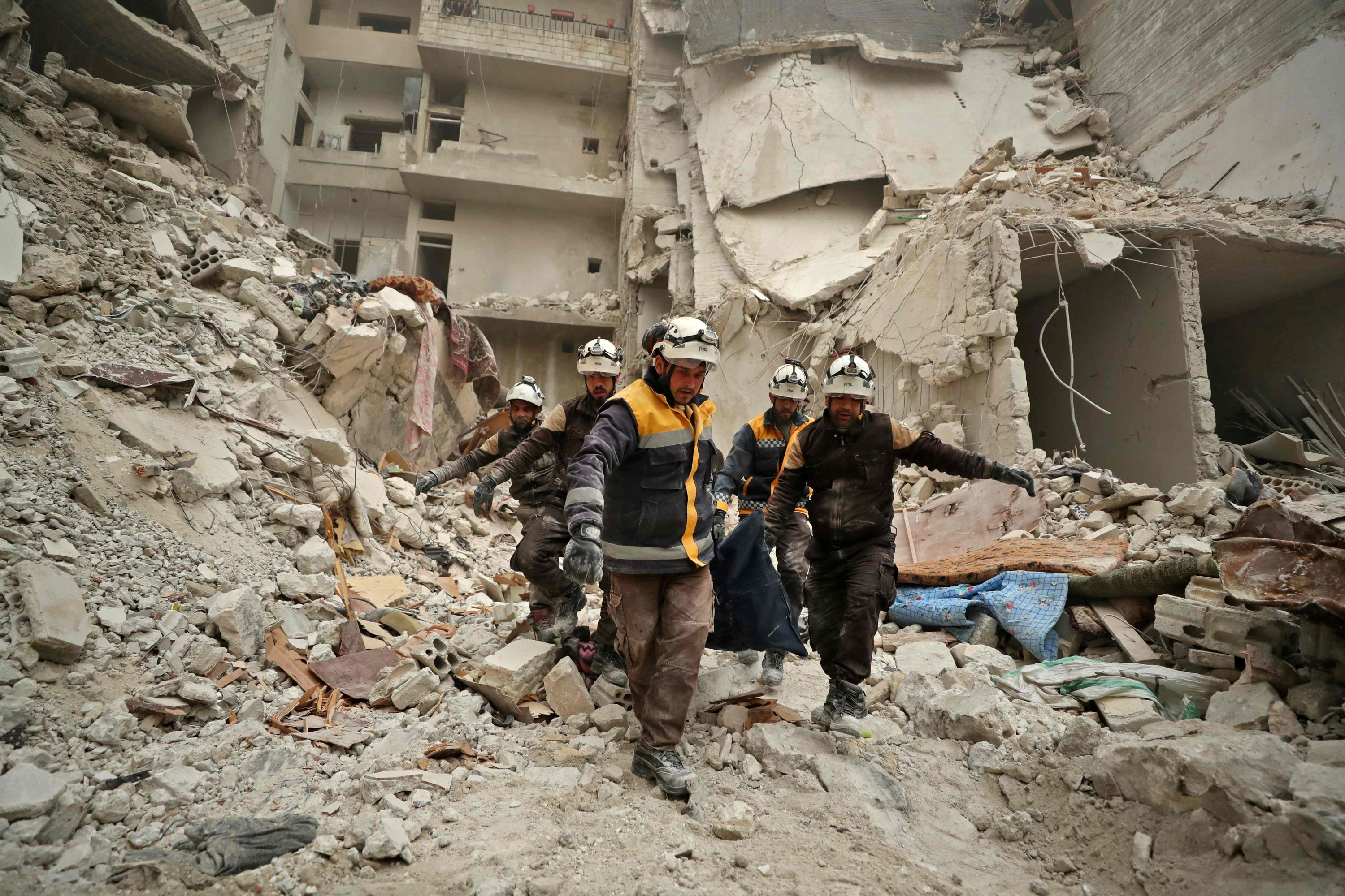 Rescue workers known as the White Helmets carry away the body of a victim found amid the rubble of a building hit during an airstrike by pro-regime forces on the opposition-held town of Ariha in the northern countryside of Idlib province, Syria, Feb. 5, 2020. (AFP Photo)