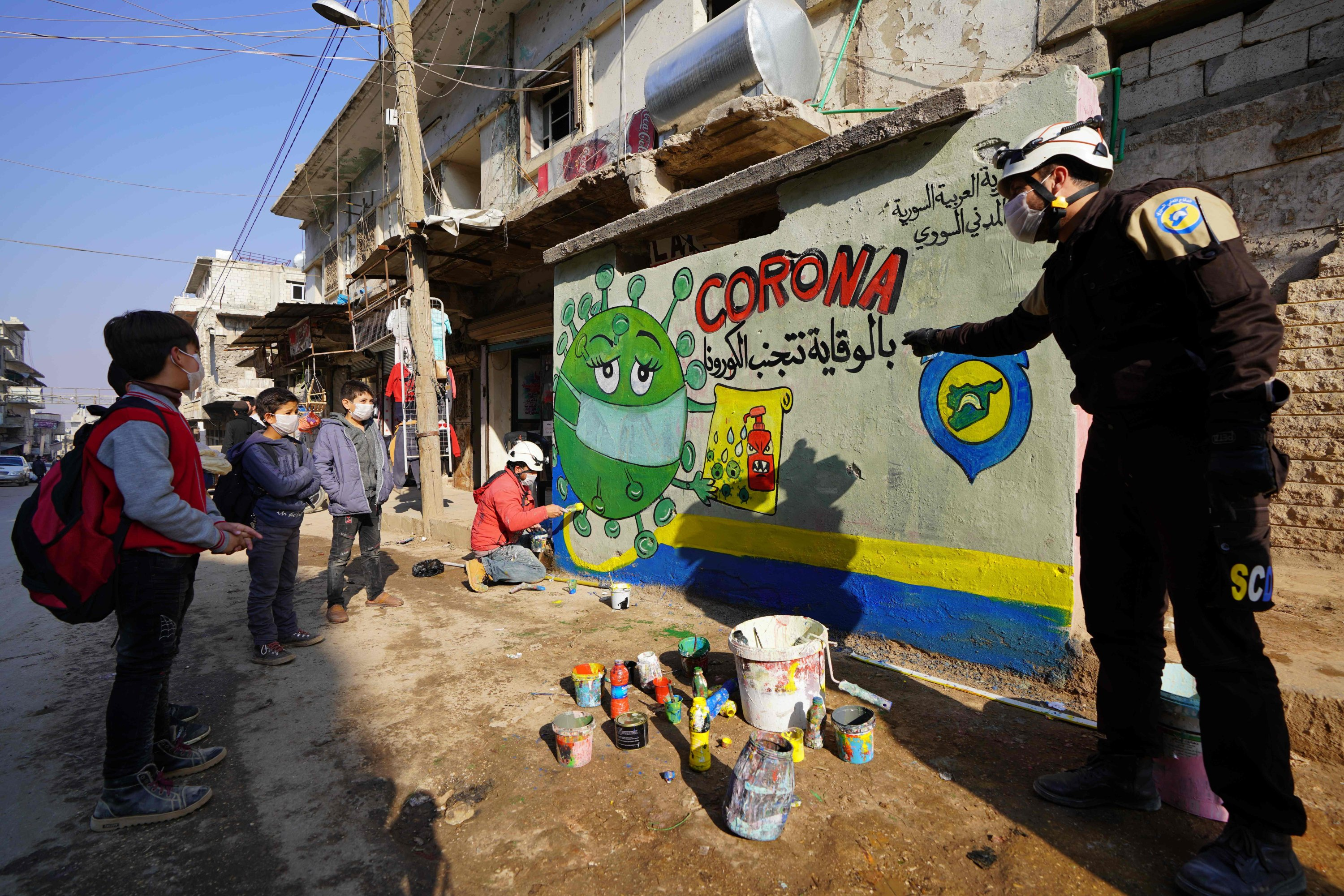 A member of the Syrian Civil Defense group known as the White Helmets instructs school children about the coronavirus during an awareness campaign organized to inform children about the COVID-19 pandemic and protection methods against the contagious virus, in the town of Binnish in northwestern Idlib province, Syria, Dec. 6, 2020. (AFP Photo)