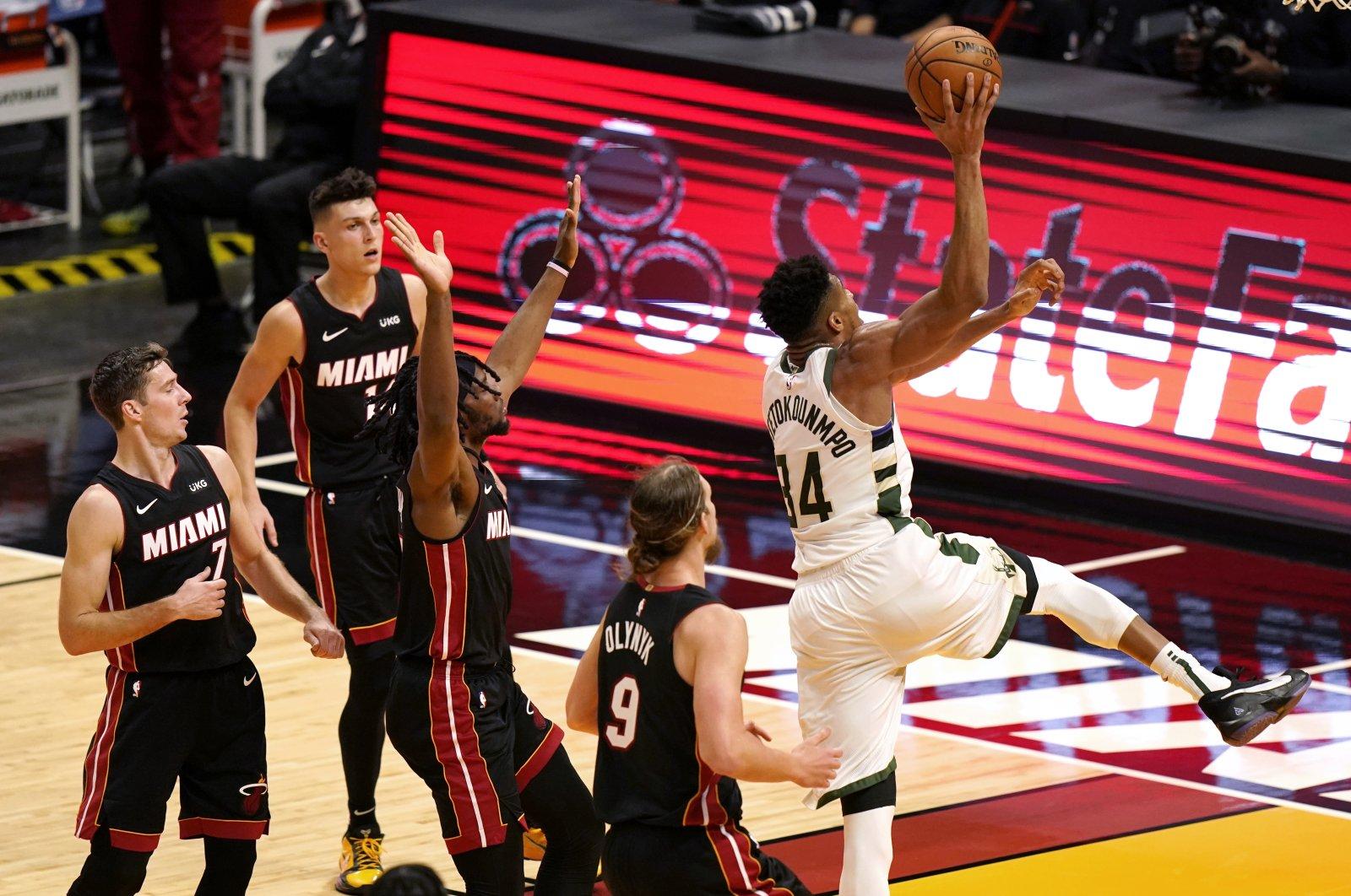 Milwaukee Bucks' Giannis Antetokounmpo (R) shoots during an NBA game against the Miami Heat, in Miami, Florida, U.S., Dec. 29, 2020. (AP Photo)