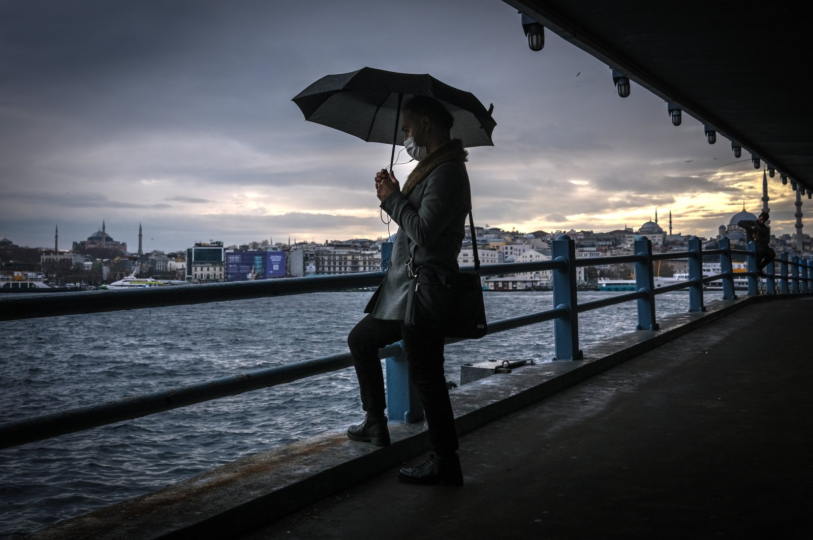 A man waits under the Galata Bridge with Hagia Sophia Grand Mosque (L) and Yeni (New) Mosque (R) in the background on a rainy day amid the ongoing coronavirus pandemic in Istanbul, Turkey, Dec. 28, 2020. (EPA Photo)