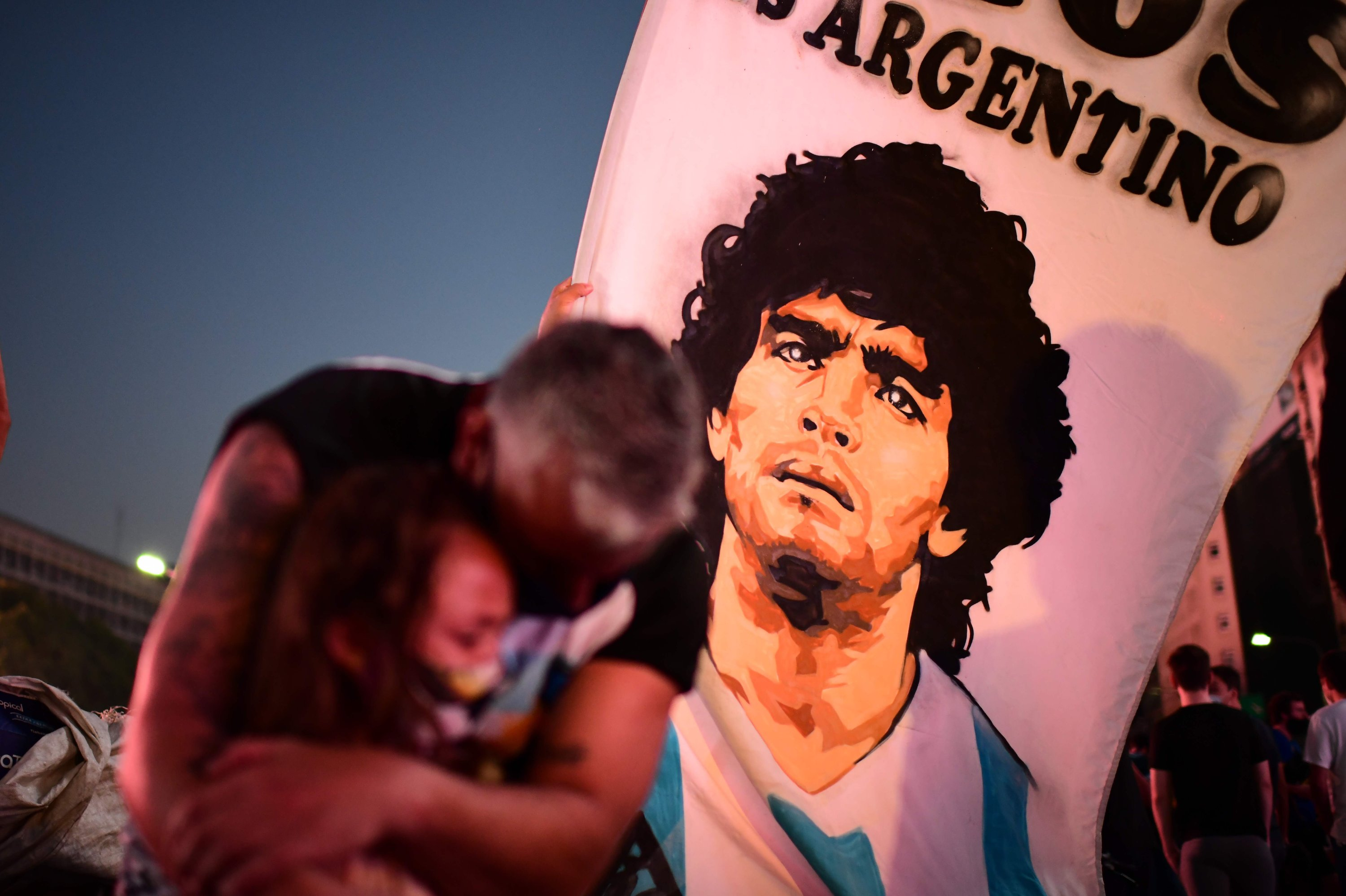 A man and his daughter, fans of Argentinian football legend Diego Maradona, mourn as they gather by the Obelisk to pay homage on the day of his death in Buenos Aires, Argentia, on Nov. 25, 2020. (AFP)
