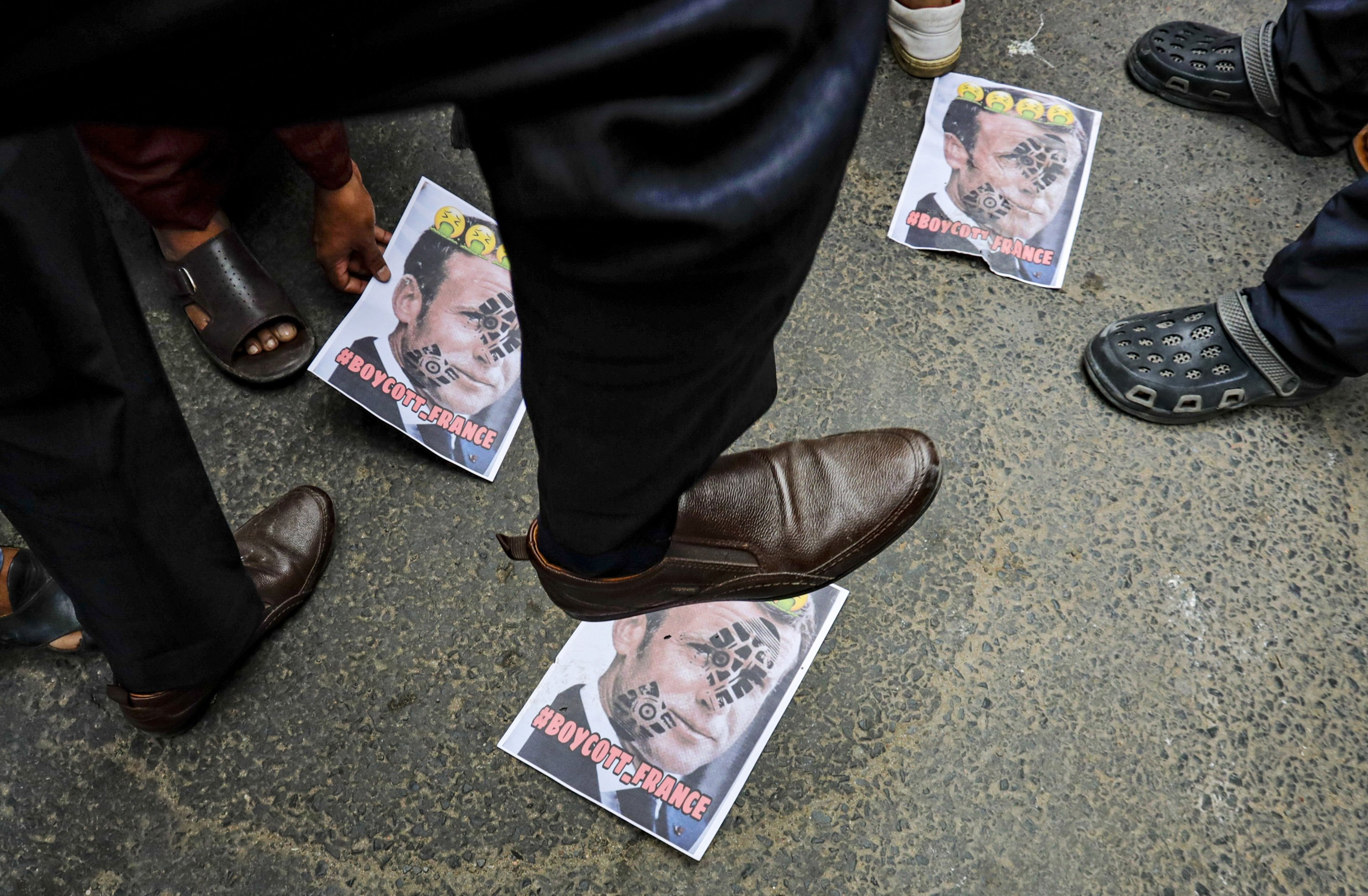 A Muslim activist stamps on posters bearing defaced images of French President Emmanuel Macron during a protest near the French Consulate, in Kolkata, India, Saturday, Oct. 31, 2020. (AP Photo)