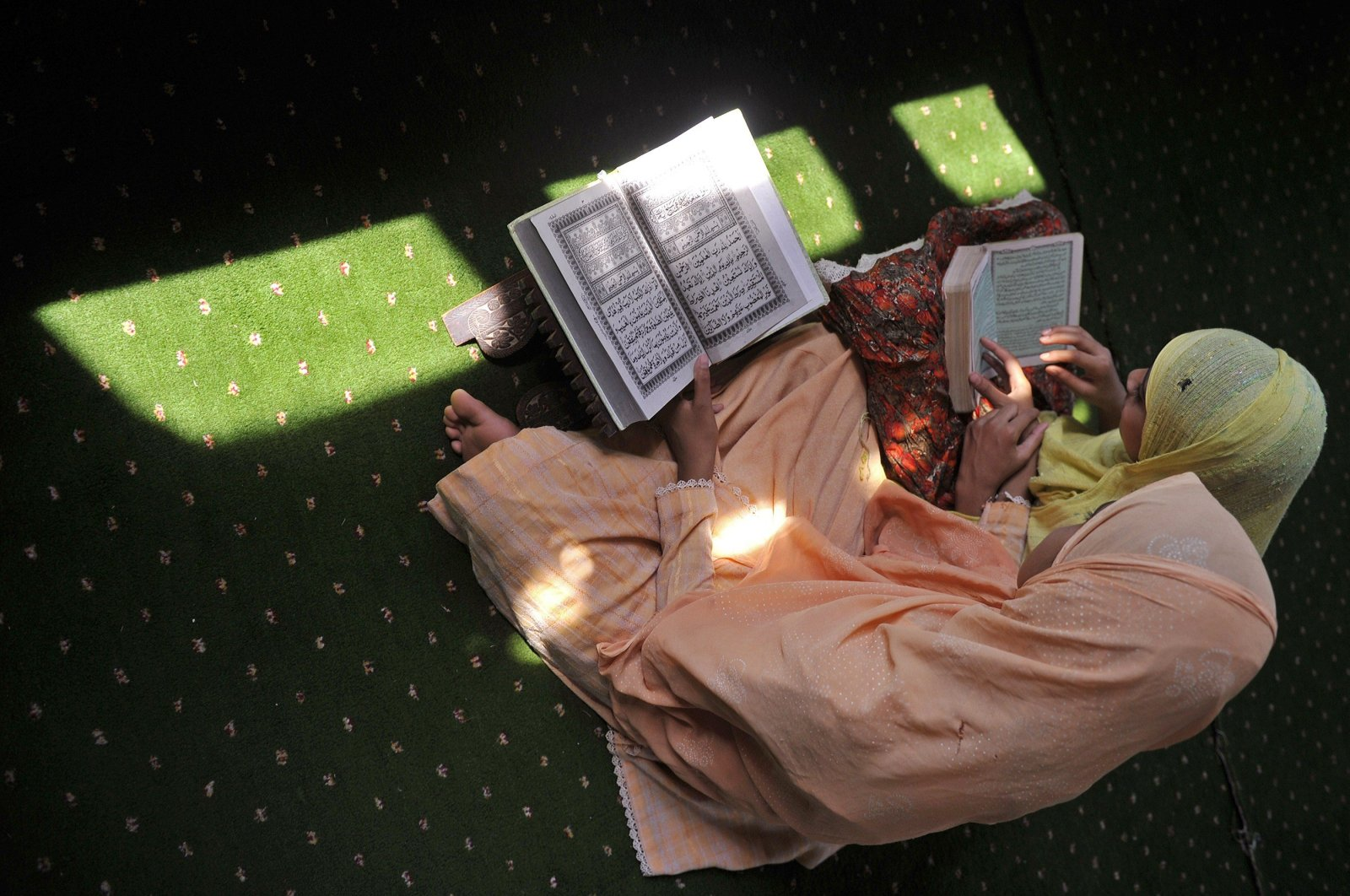 Two Kashmiri Muslim women read the Quran at the Shahi Hamdaan shrine on the first Friday of Ramadan in Srinagar on Aug. 5, 2011. (AFP Photo)