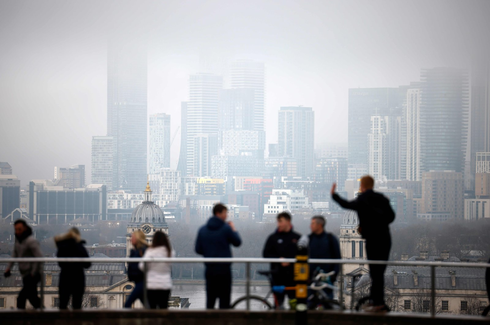 People walk in Greenwich Park with the office buildings of the Canary Wharf financial district in the background in London, U.K., Dec. 28, 2020. (AFP Photo)