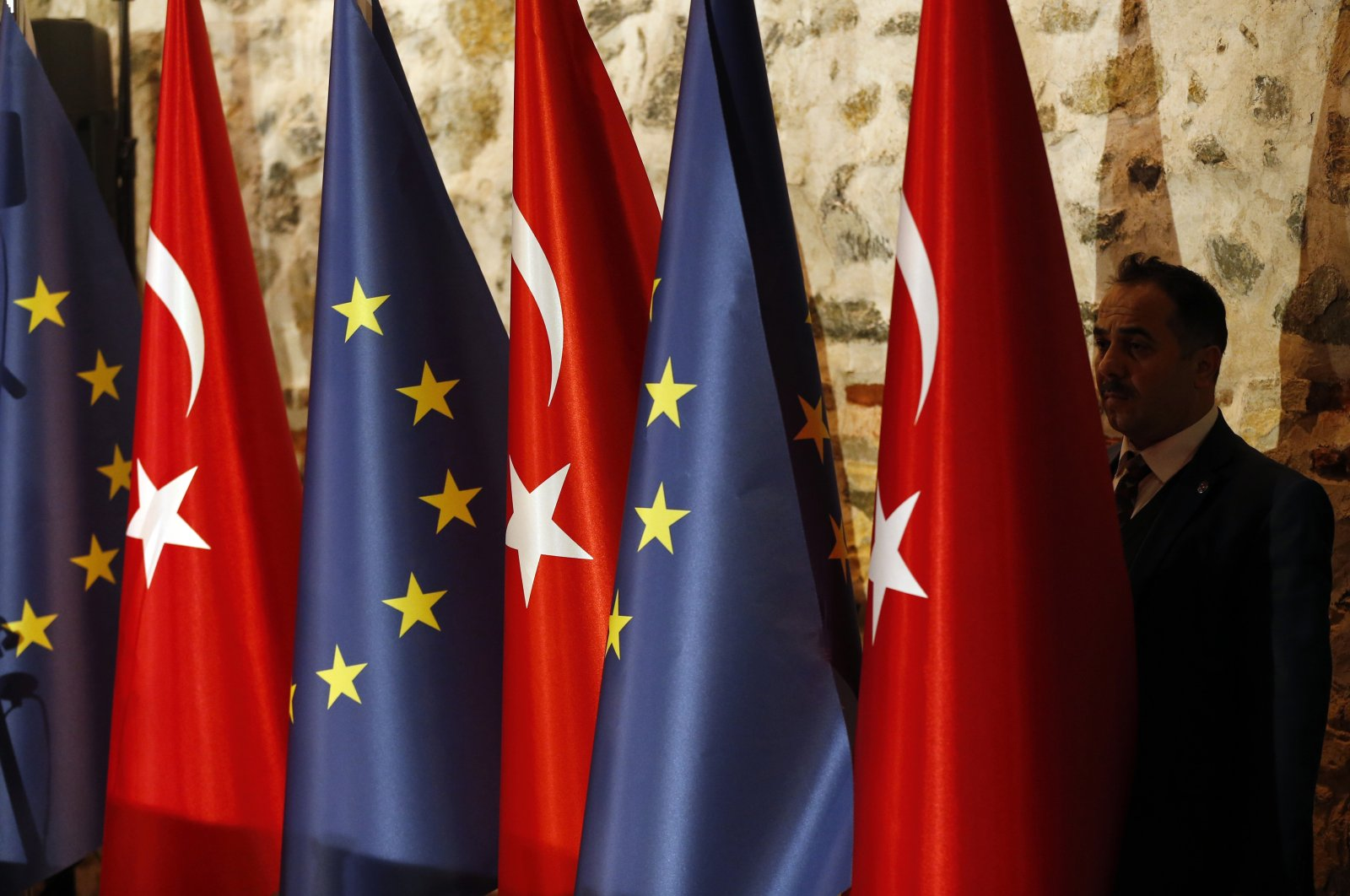 An official adjusts the flags of Turkey and the European Union prior to a bilateral meeting, Istanbul, Turkey, Feb. 28, 2019. (AP Photo)