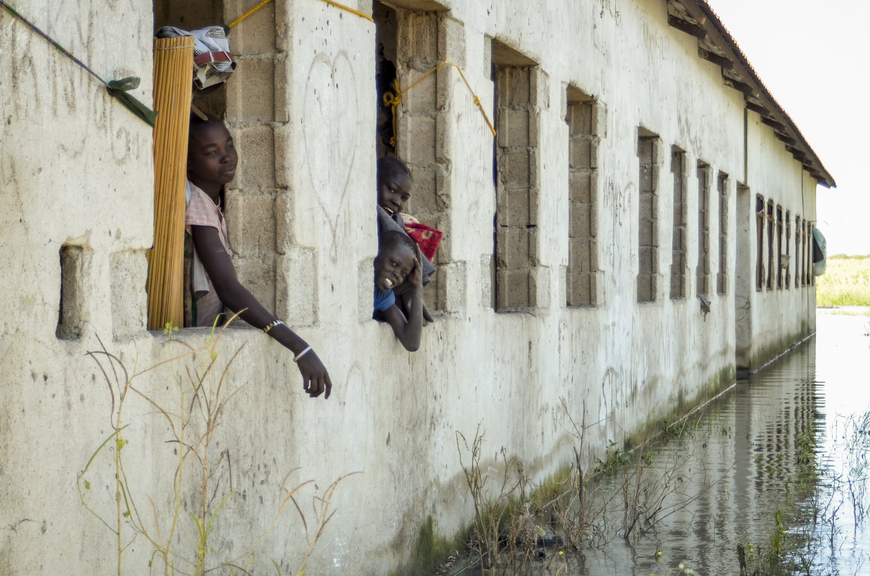 A young girl and her siblings look out at floodwaters surrounding the primary and nursery school where they are living in the village of Wang Chot, Old Fangak county, Jonglei state, South Sudan, Nov. 26, 2020. (AP Photo)