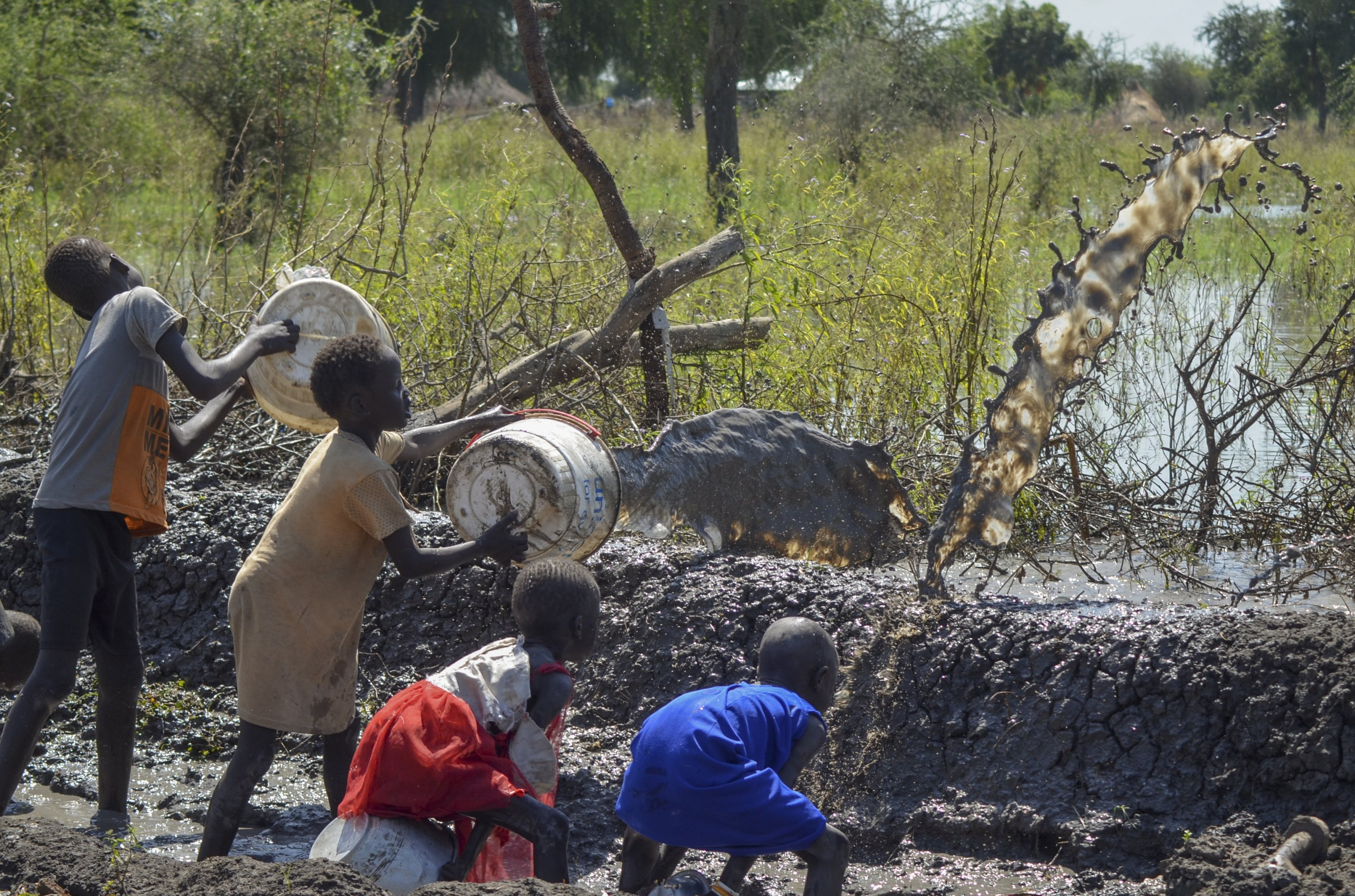 Children use buckets to clear muddy floodwater from a dyke in the village of Wang Chot, Old Fangak county, Jonglei state, South Sudan, Nov. 26, 2020. (AP Photo)