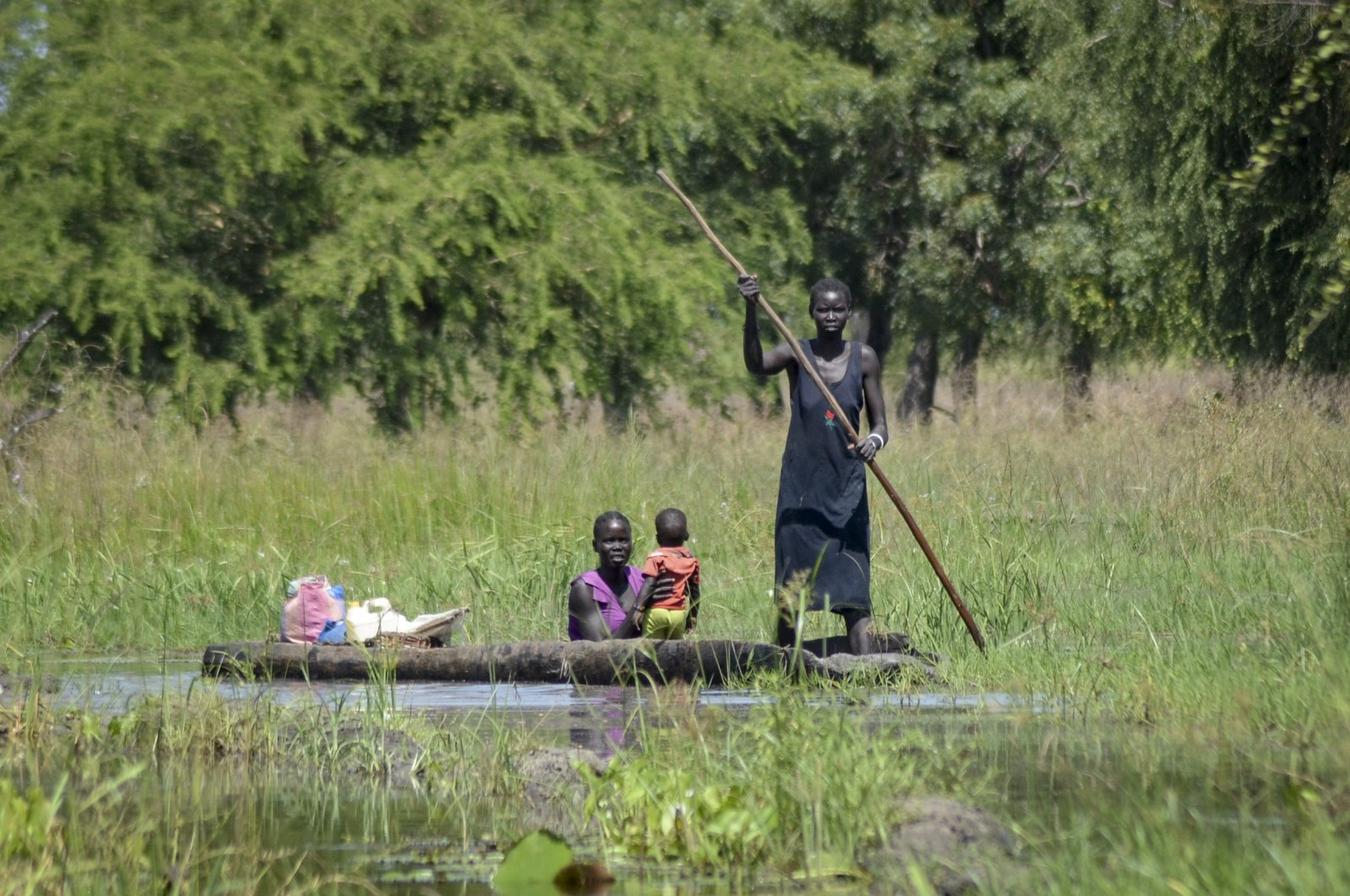 A mother holds her baby as she is transported by dugout canoe through floodwaters in the village of Wang Chot, Old Fangak county, Jonglei state, South Sudan, Nov. 26, 2020. (AP Photo)