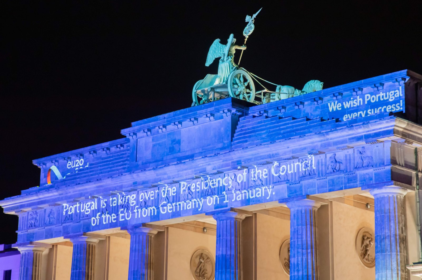 A photo taken on New Year's Eve, December 31, 2020 shows Berlin's landmark Brandenburg Gate illuminated to mark the end of Germany's EU presidency. (AFP Photo)