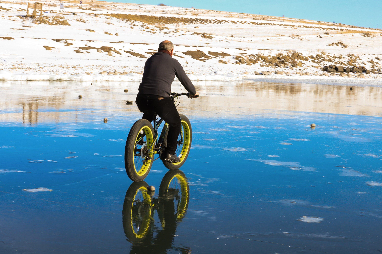 A man rides a wide-tired bicycle across the frozen surface of Lake Çıldır in the Çıldır district of Ardahan province, eastern Turkey, Dec. 28, 2020. (IHA Photo)