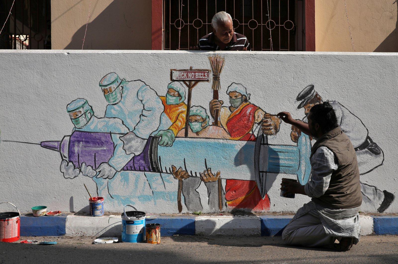 A man applies finishing touches to graffiti representing a vaccine, amidst the spread of coronavirus disease (COVID-19) in Kolkata, India, Jan. 2, 2021. (Reuters Photo)