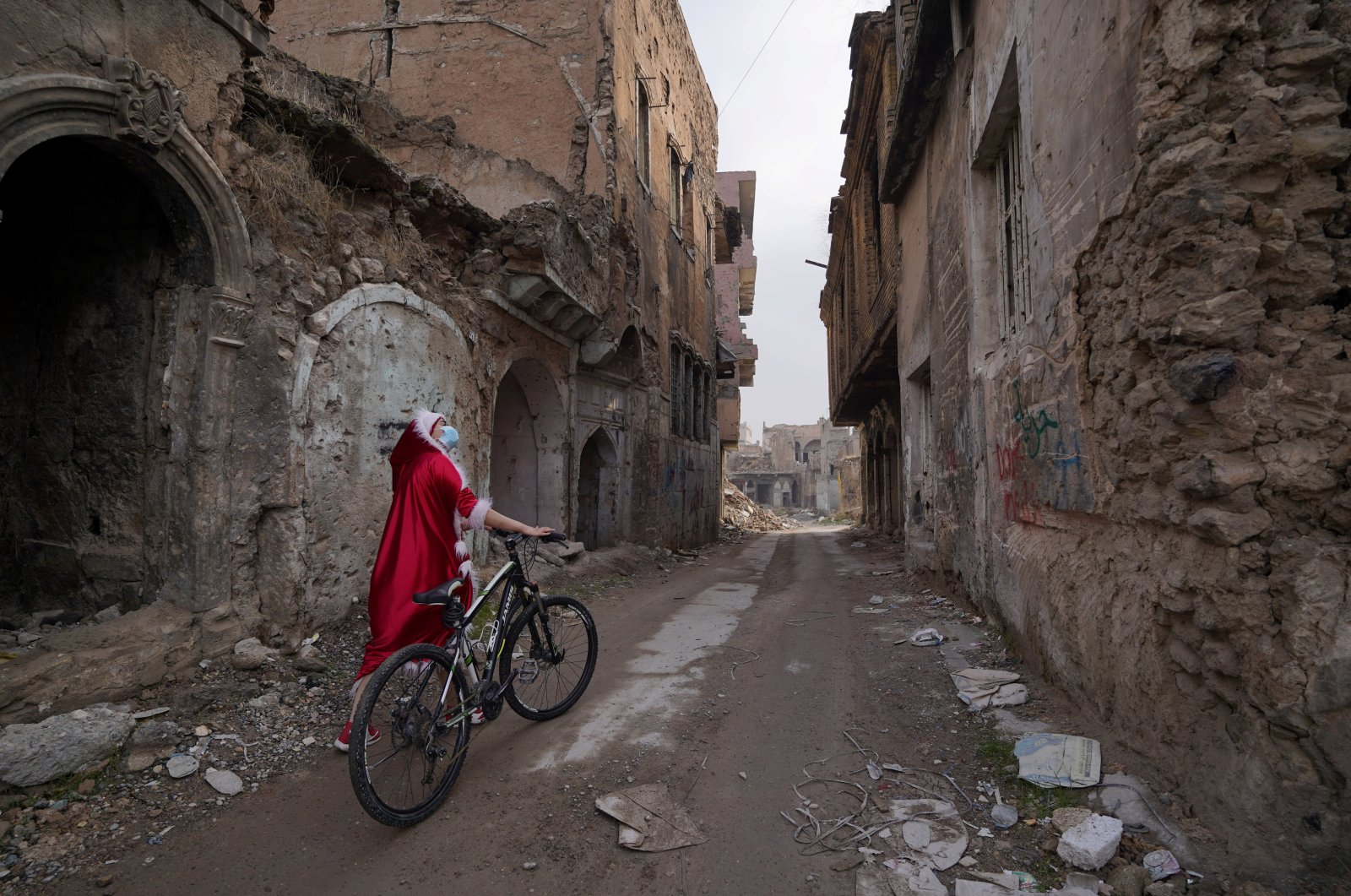 An Iraqi woman, dressed as Santa Claus, looks at the destroyed buildings as she walks with her bicycle in the old city of Mosul, Iraq, Dec. 18, 2020. (Reuters Photo)