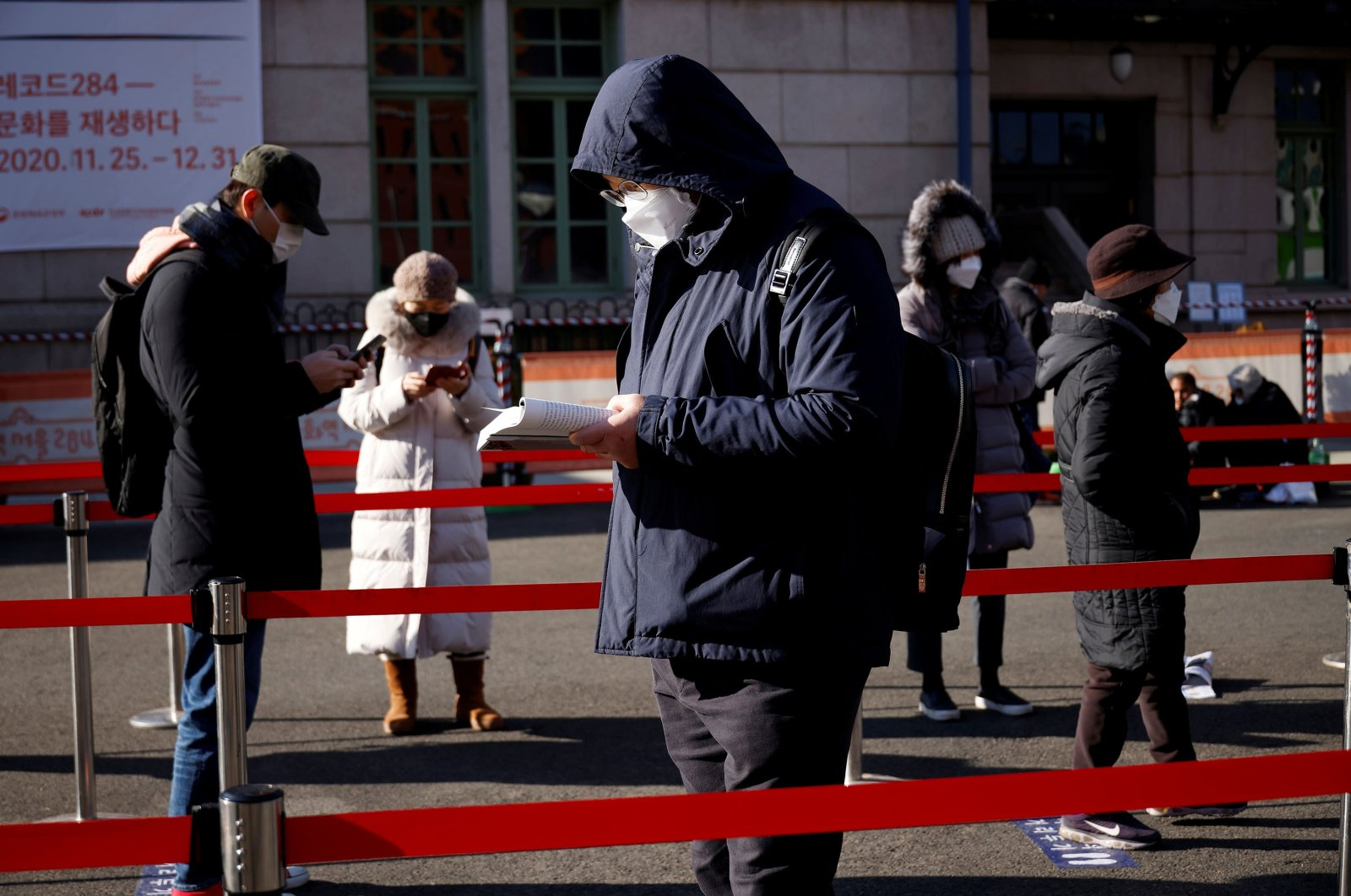 A man reads a book while waiting in a line to undergo a coronavirus test at a testing site which is temporarily set up in front of a railway station on Christmas Day in Seoul, South Korea, Dec. 25, 2020. (Reuters Photo)