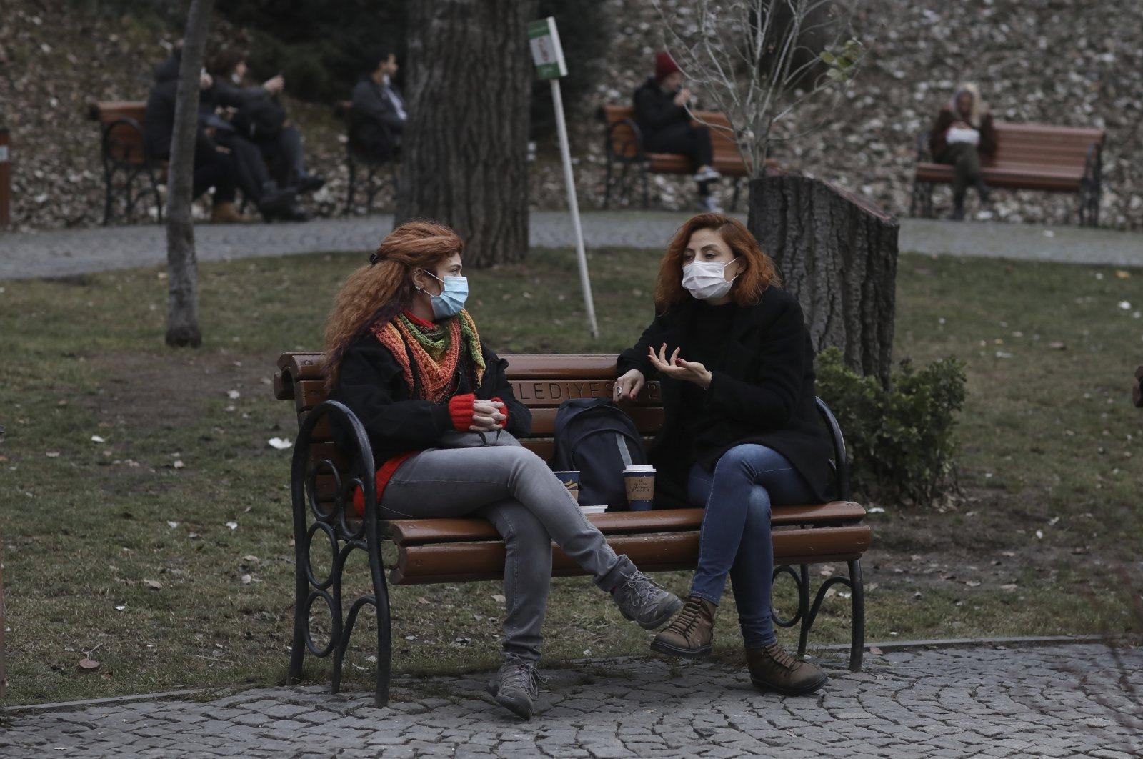 Women wearing protective masks sit in a park in the capital Ankara, Turkey, Dec. 31, 2020. (AP PHOTO)