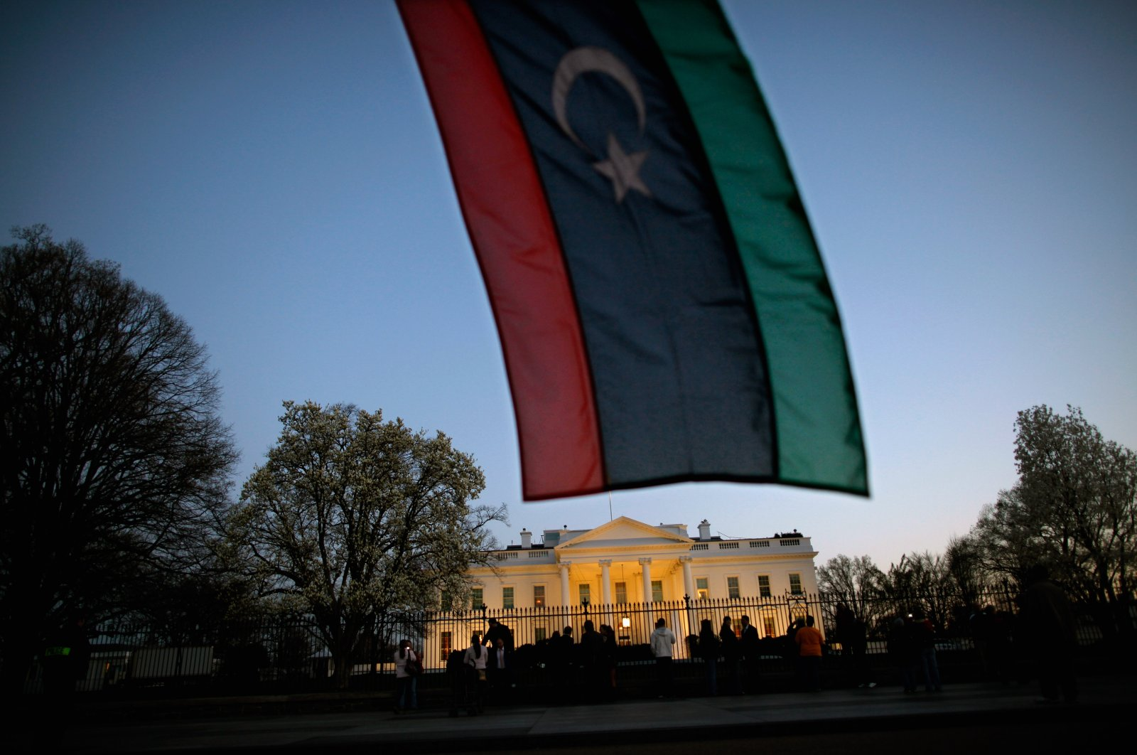 A Libyan holds up a Libyan flag while standing in front of the White House as then-President Barack Obama comments on U.S. involvement in Libya, Washington, D.C., March 28, 2011. (Getty Images)