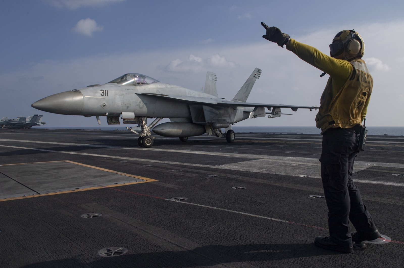 Aviation Boatswain's Mate 3rd Class Marnell Maglasang directs an F/A-18E Super Hornet on the flight deck of the aircraft carrier USS Nimitz in the Arabian Sea, Nov. 27, 2020. (Mass Communication Specialist 3rd Class Cheyenne Geletka/U.S. Navy via AP)
