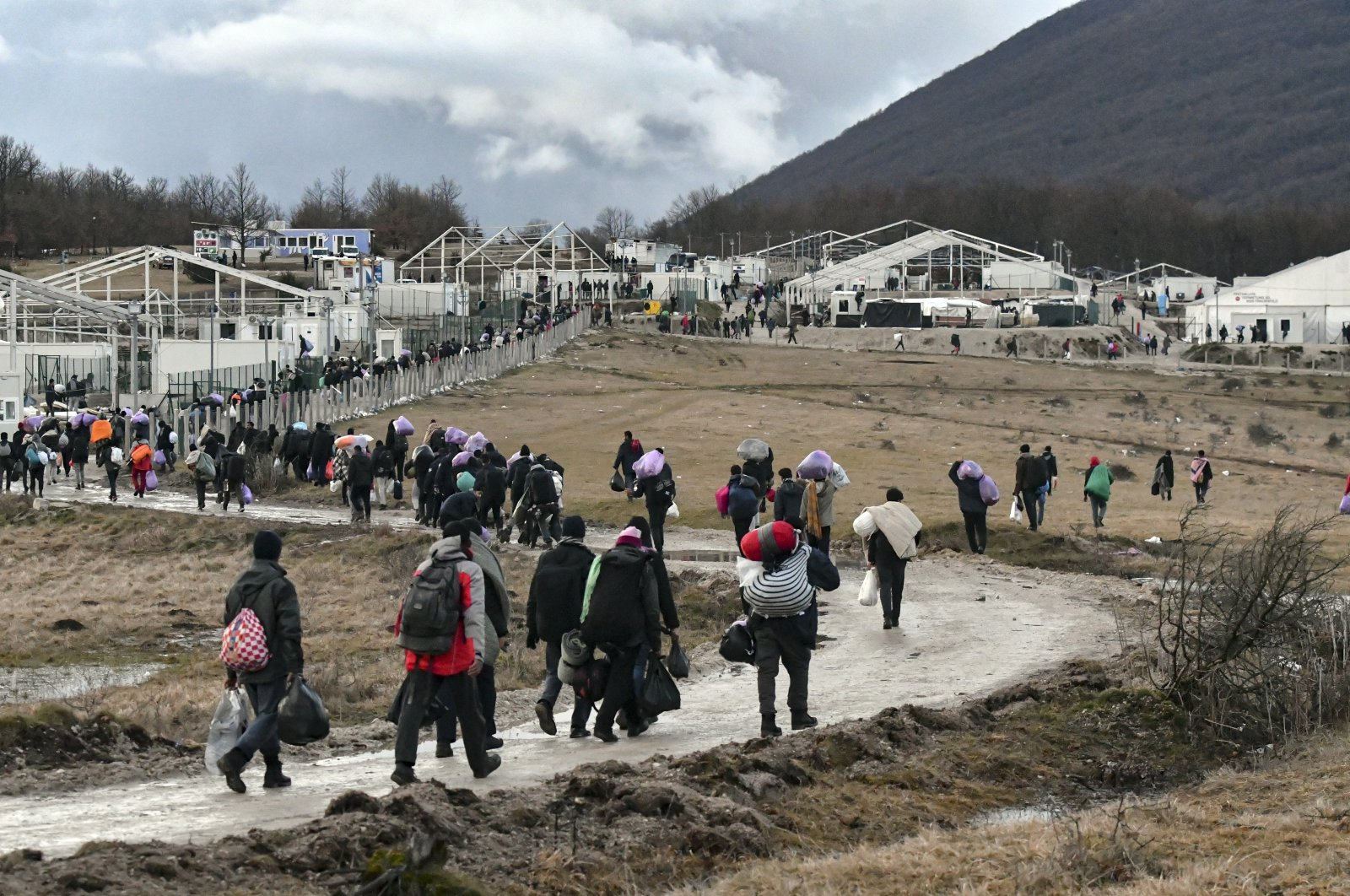 Migrants walk back to the Lipa camp after hundreds failed to be relocated from the burnt-out tent camp in the northwest of the country, outside Bihac, Bosnia-Herzegovina, Dec. 30, 2020. (AP Photo)