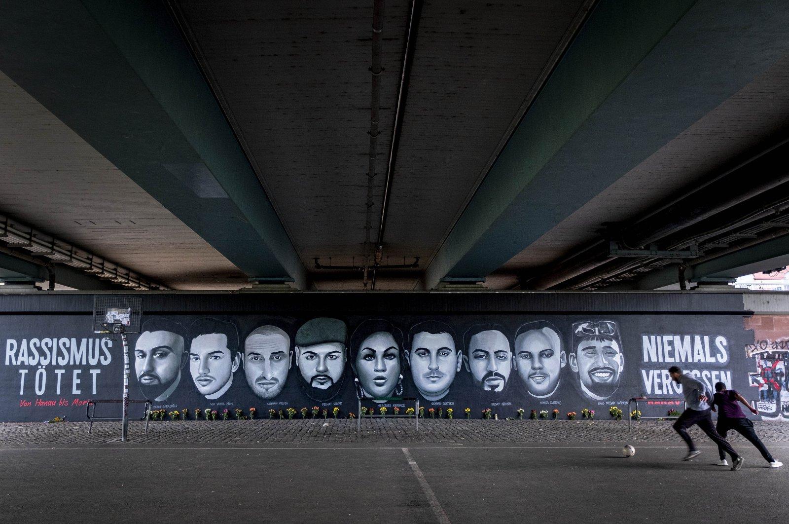 A boy and a man play football near graffiti depicting the nine victims of the Hanau shooting, under a bridge in Frankfurt am Main, Germany, June 20, 2020. (AP Photo)