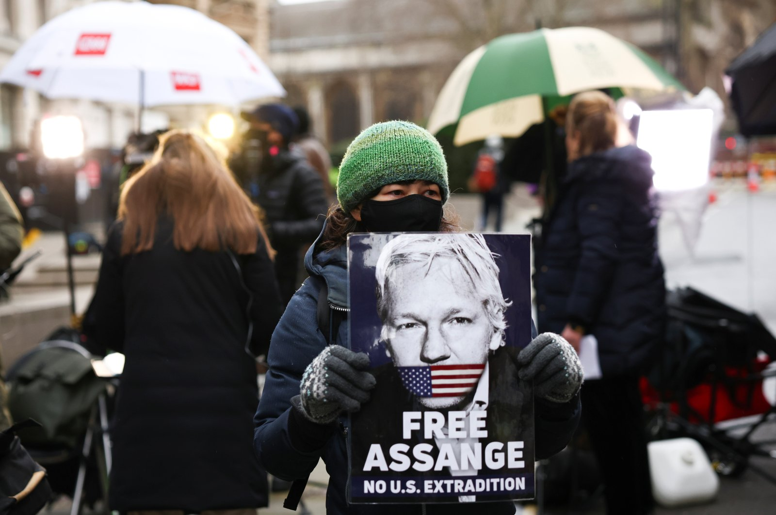 A supporter of WikiLeaks founder Julian Assange holds a placard, at the Old Bailey, the Central Criminal Court, in London, Britain, Jan. 4, 2021. (Reuters Photo)