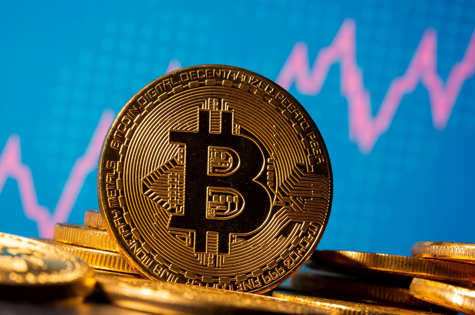 A representation of virtual currency Bitcoin is seen in front of a stock graph in this illustration taken Nov. 19, 2020. (Reuters Photo)