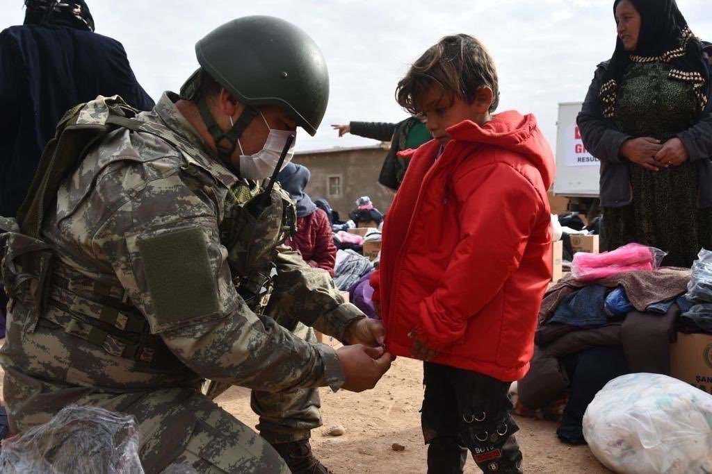 Turkish soldiers distribute food and clothing in northern Syria's Operation Peace Spring area, Jan. 4, 2021. (AA Photo)