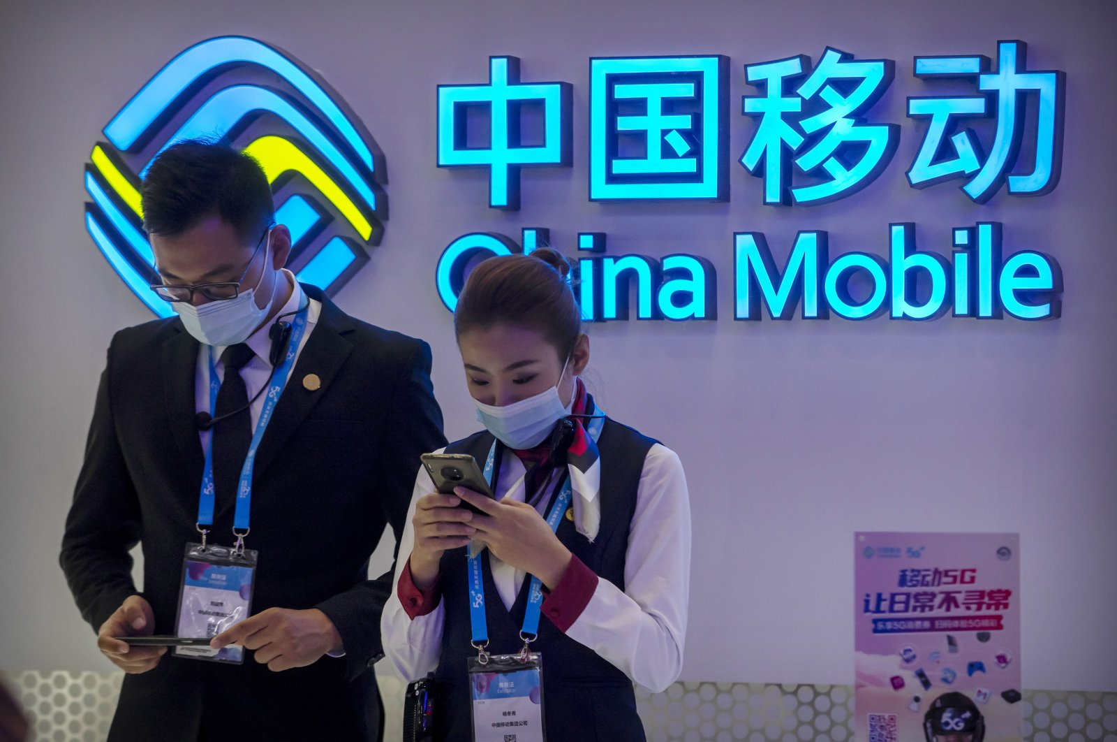 Staff members wearing face masks to protect against the spread of the coronavirus use their smartphones near a sign for Chinese telecommunications firm China Mobile at the PT Expo in Beijing, China, Oct. 14, 2020. (AP Photo)