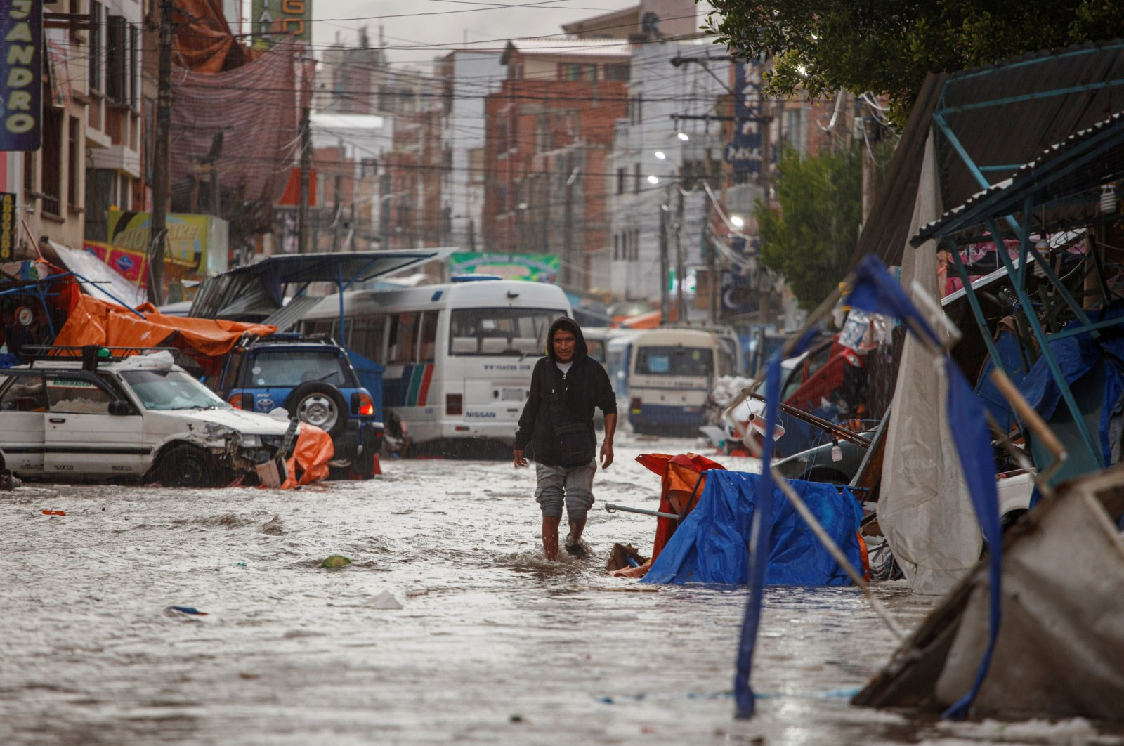 A man walks along a street flooded by heavy rains in Sucre, Bolivia January 4, 2021. (Correo del Sur/Carlos Rodriguez/Handout via REUTERS)