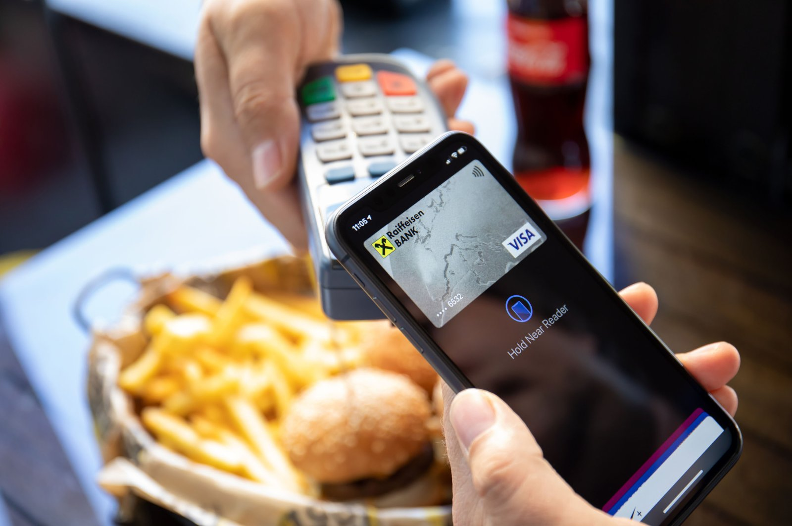 A man holds his smartphone with Apple Pay on the screen to make an online payment, Antalya, southern Turkey, Oct. 13, 2020. (Shutterstock Photo)