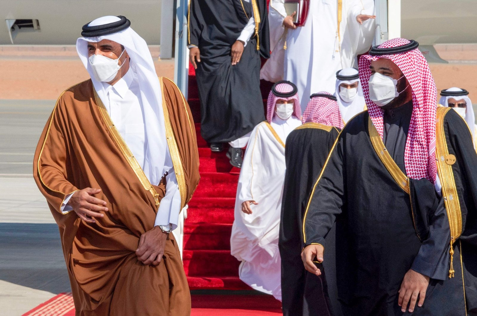 A handout photo made available by the Saudi Royal Court shows Saudi Arabia's Crown Prince Mohammed bin Salman welcoming Emir of Qatar, Sheikh Tamim bin Hamad Al Thani upon his arrival to attend the 41st annual six-member Gulf Cooperation Council (GCC) Summit at Al-Ula, Saudi Arabia, Jan. 5, 2021. (AFP Photo)