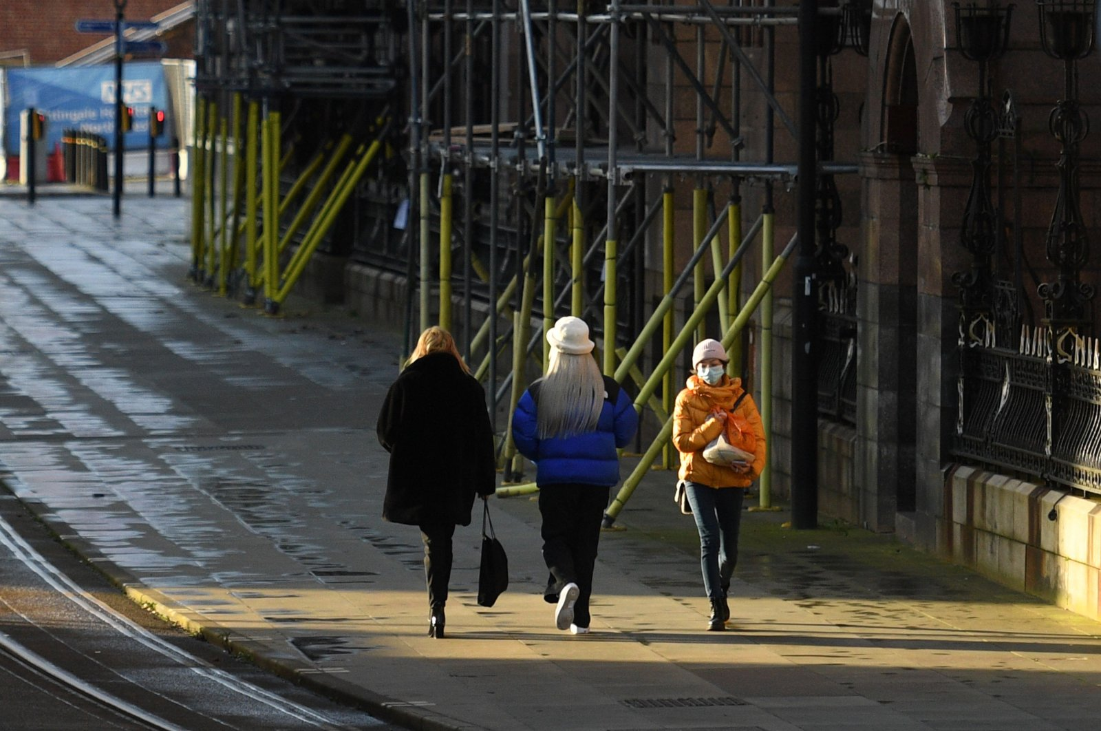 Pedestrians, some wearing masks or face coverings, walk along an almost empty street in Manchester, north west England on Jan. 5, 2021, as Britain enters a second national lockdown to combat the spread of COVID-19. (AFP Photo)