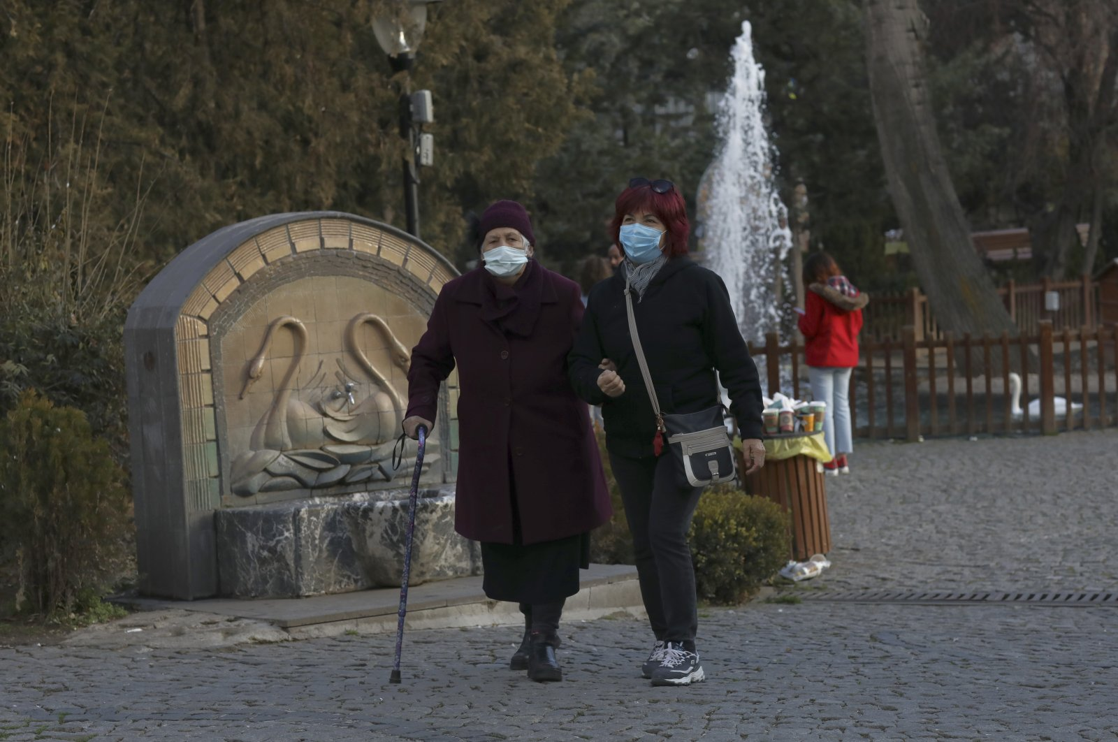 Women wearing face masks walk in a public garden in Ankara, Turkey, Jan. 1, 2021. (AP Photo)