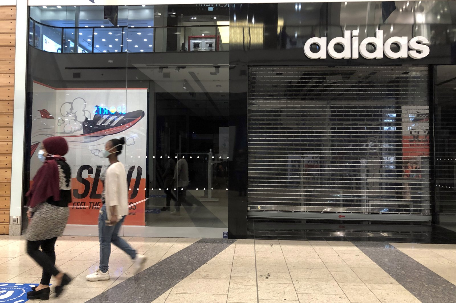 Women pass by a closed branch of sportswear company Adidas, in Beirut, Lebanon, Dec. 7, 2020. (EPA Photo)
