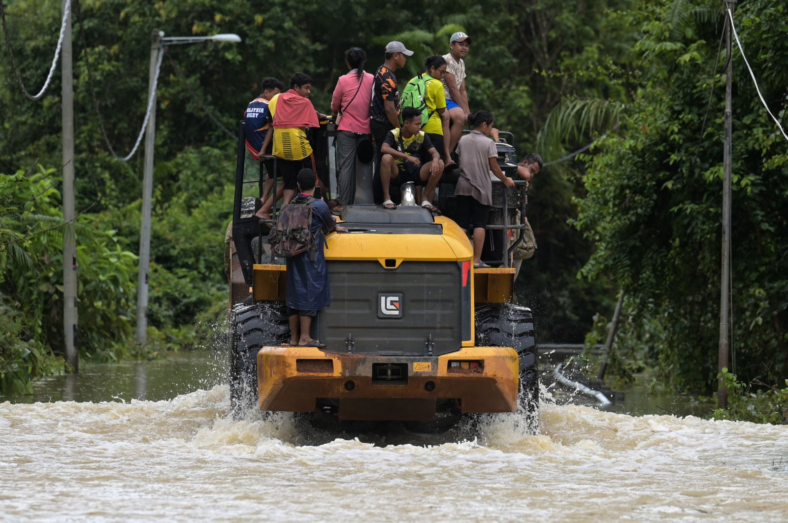 Residents ride a digger vehicle through floodwaters following a heavy monsoon downpour in Lanchang, Malaysia's Pahang state on Jan. 6, 2021. (AFP Photo)