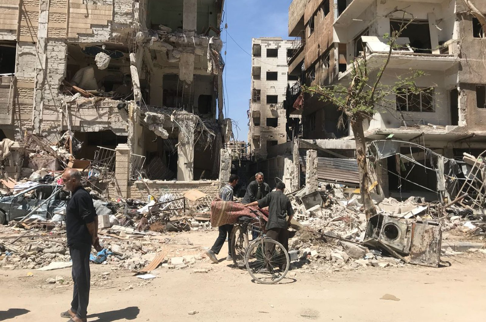 People stand in front of damaged buildings, in the town of Douma, the site of a suspected chemical weapons attack, near Damascus, Syria, April 16, 2018. (AP)