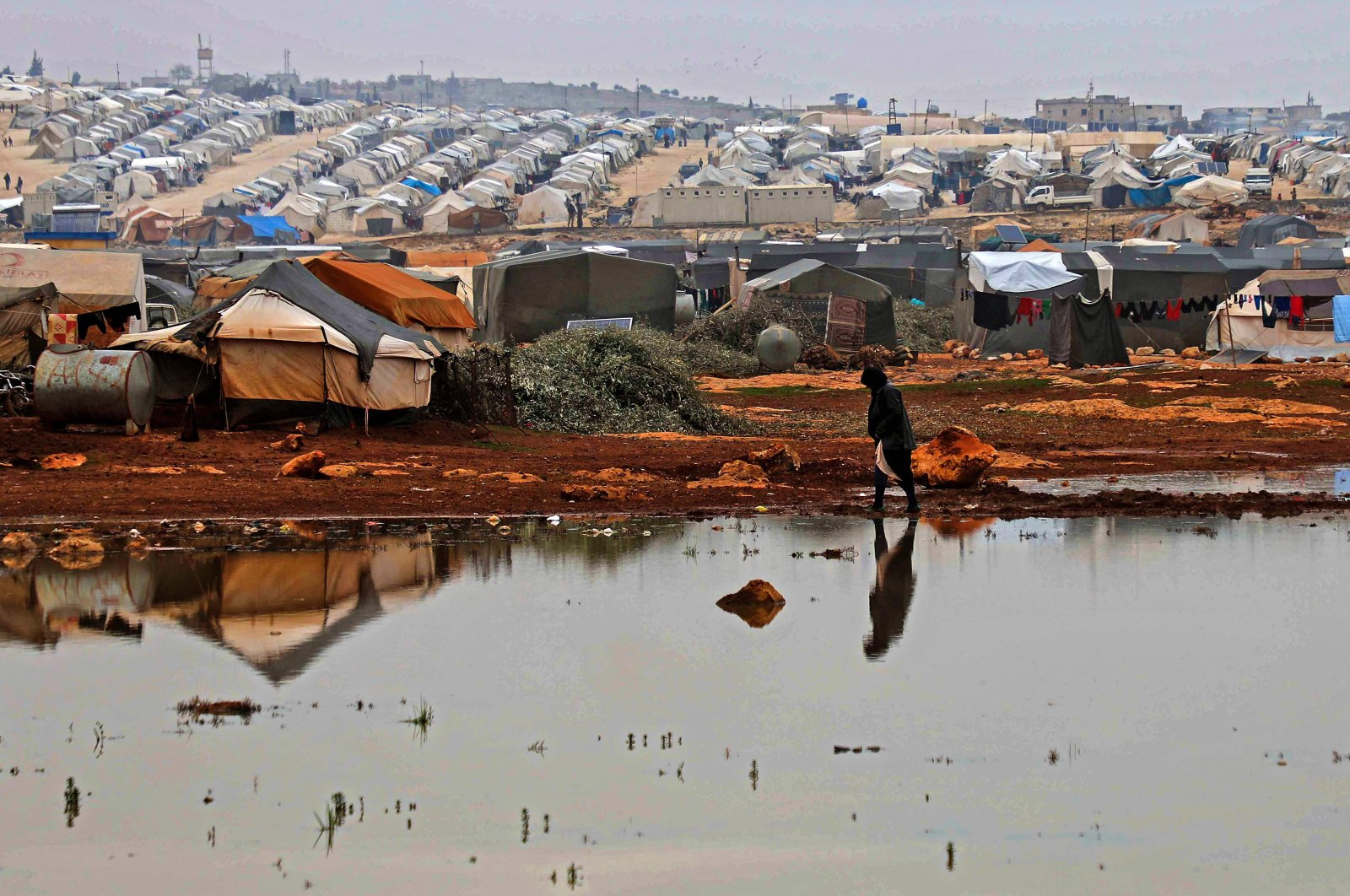 A Syrian woman walks on a flooded patch at a camp for displaced Syrians near the town of Kafr Lusin by the border with Turkey, in Syria's opposition-held northwestern province of Idlib, Dec. 15, 2020. (AFP Photo)