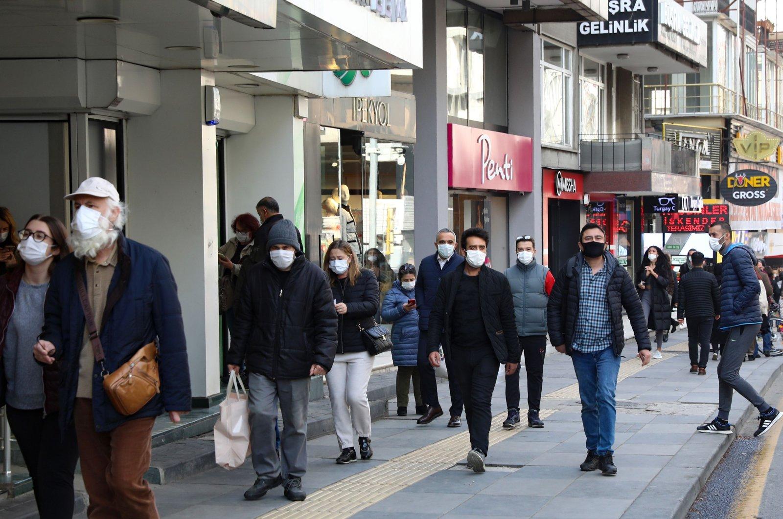 People wearing protective face masks walk on a street in the capital Ankara, Turkey, Jan. 4, 2021. (AFP Photo)