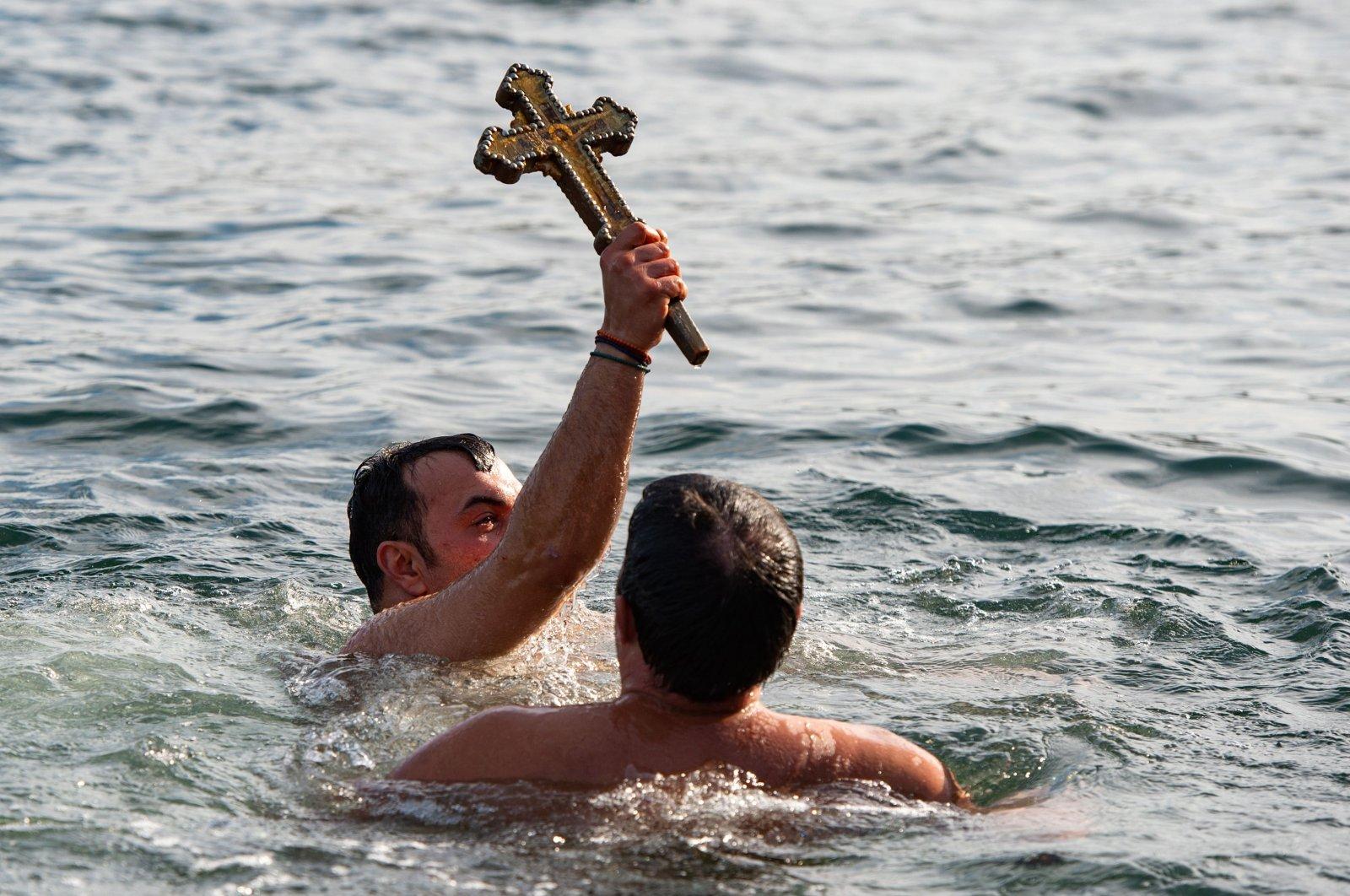 Orthodox faithful Vasili Kürkçü celebrates as he retrieves the wooden cross, in Istanbul, Turkey, Jan. 6, 2021. (AFP Photo)