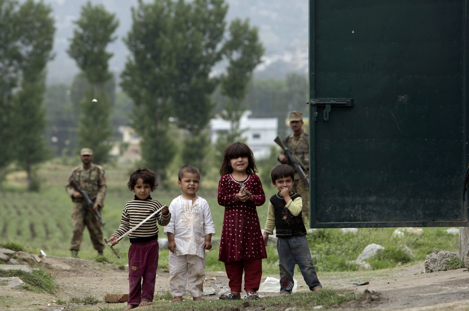 Children look on while playing as Pakistani army soldiers stand guard around the house where al-Qaida leader Osama bin Laden was caught and killed in Abbottabad, Pakistan, May 6, 2011. (AP Photo)