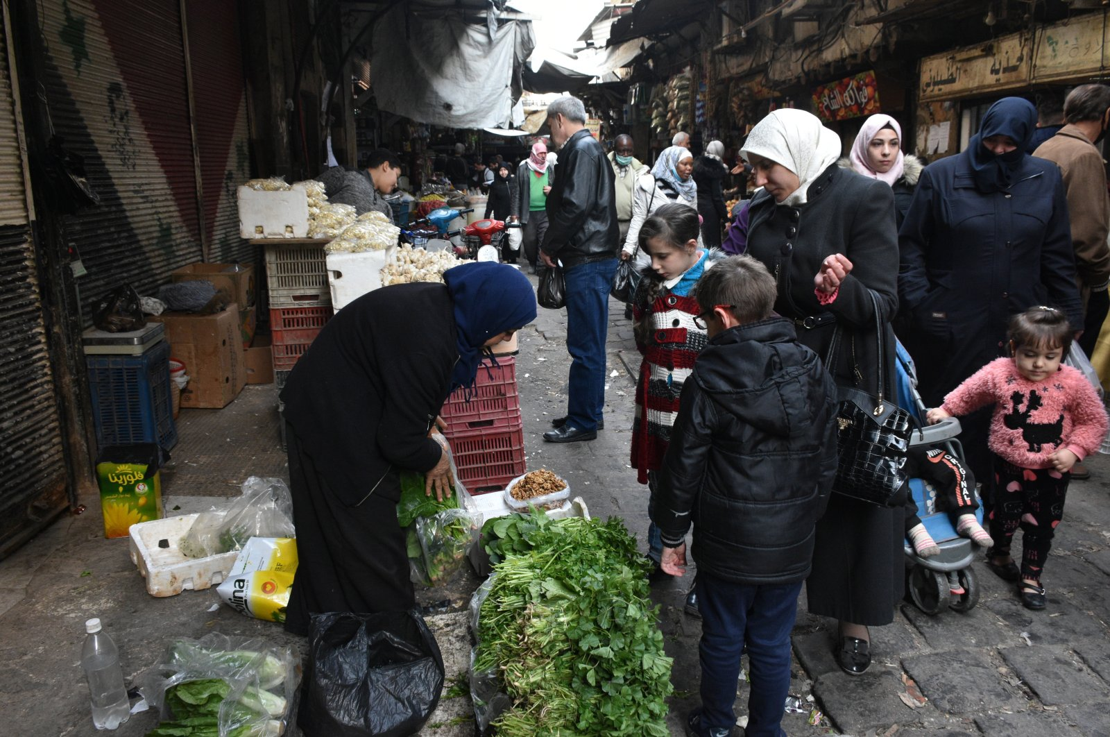 Syrians buy basic food items and other necessities on a street in Damascus, Syria, Jan. 5, 2021.  (EPA Photo)