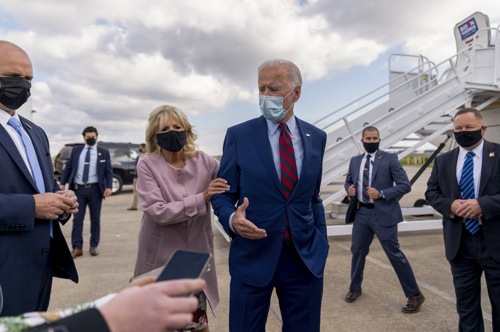 Jill Biden moves her husband, Democratic presidential candidate former Vice President Joe Biden, back from members of the media as he speaks outside his campaign plane in New Castle, Del., on Oct. 5, 2020. (AP Photo)