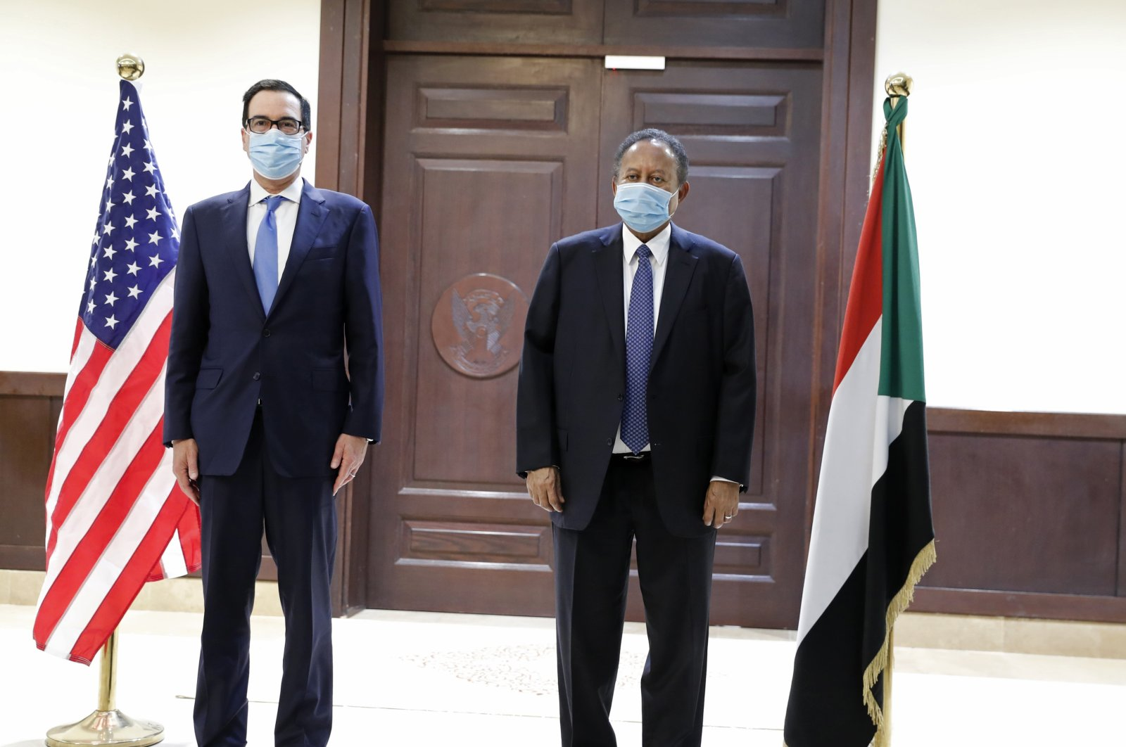 Sudanese Prime Minister Abdullah Hamdok (R) welcomes U.S. Treasury Secretary Steven Mnuchin to the Cabinet Building, in Khartoum, Sudan, Jan. 6, 2021. (AP Photo)